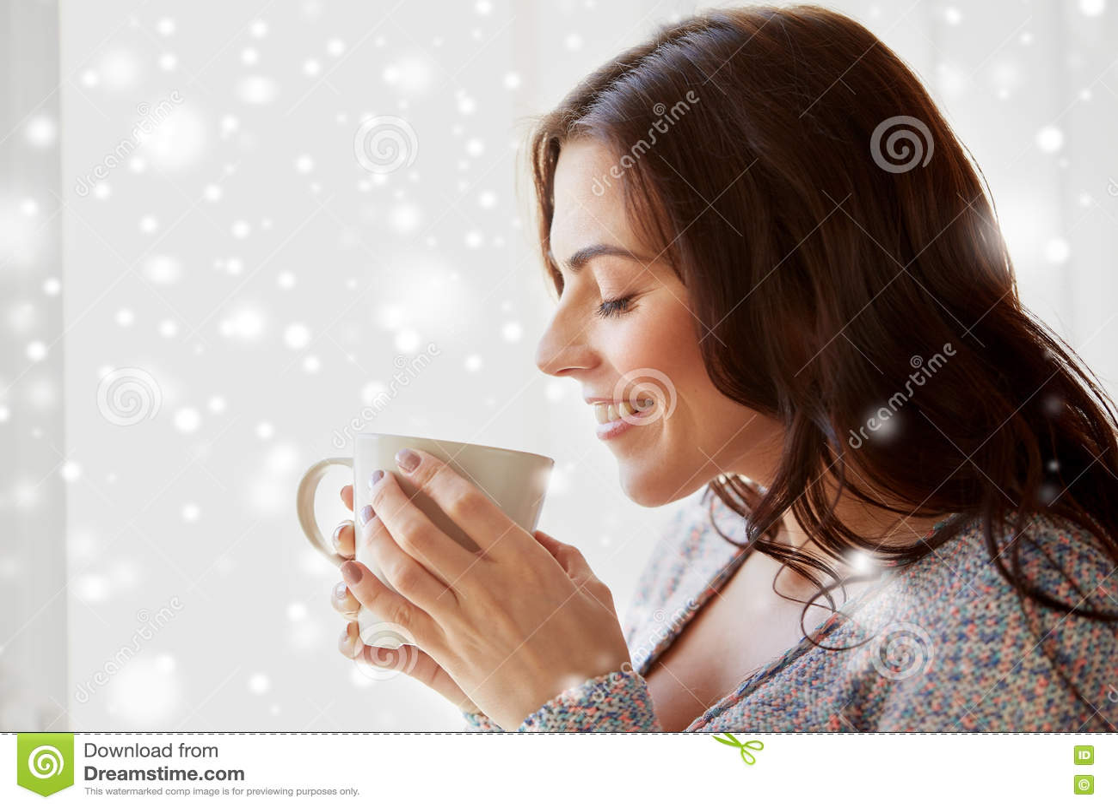 Mulher feliz com o copo do chá ou do café em casa