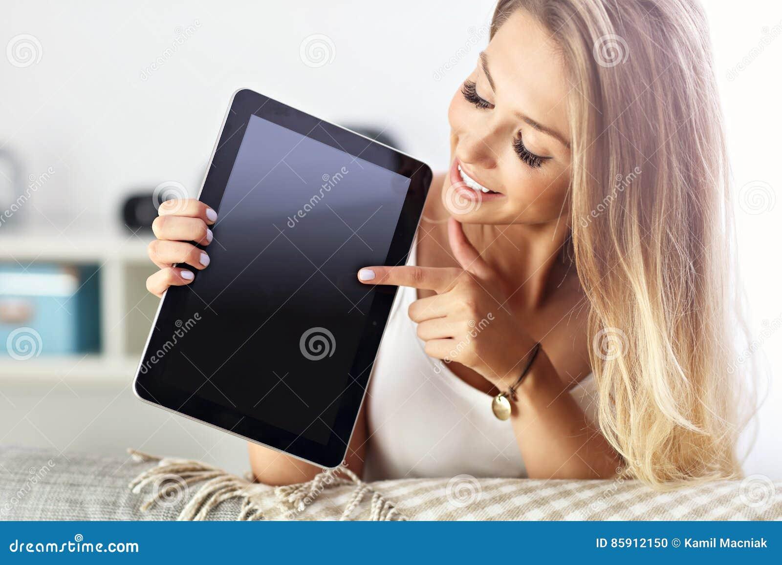 Mulher feliz com a tabuleta no sofá