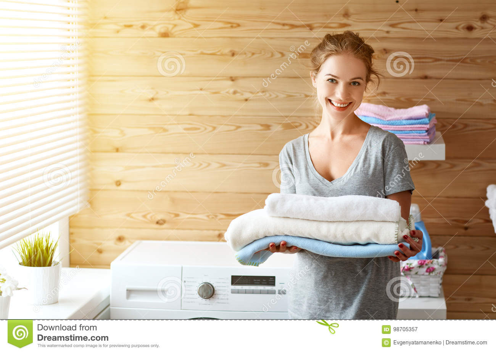 Mulher feliz da dona de casa na lavandaria com máquina de lavar