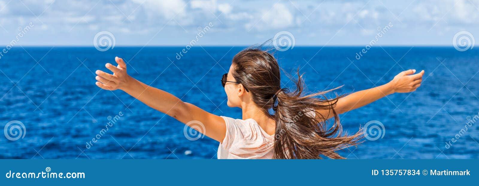 Mulher feliz da liberdade com os braços abertos que olham o mar