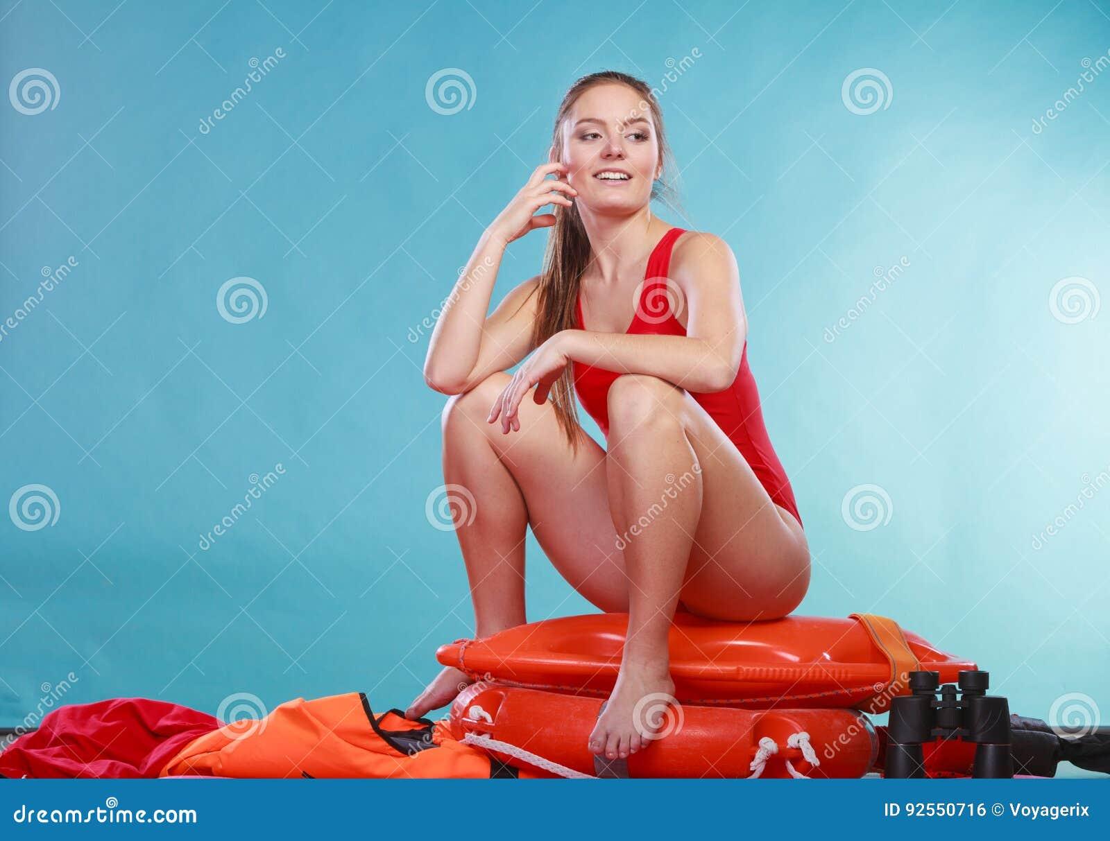 Mulher feliz da salva-vidas que senta-se na boia de anel do salvamento