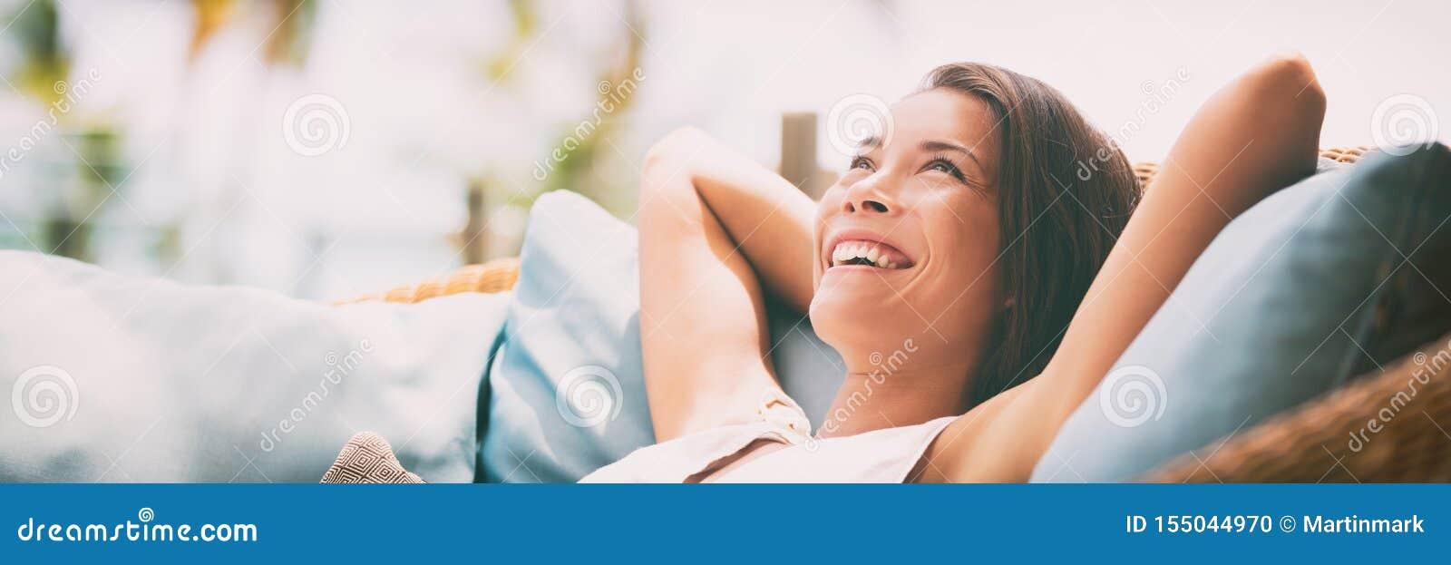 A mulher feliz de relaxamento do estilo de vida da casa relaxa dentro o sofá da sala de hotel de luxo que encontra-se para trás c