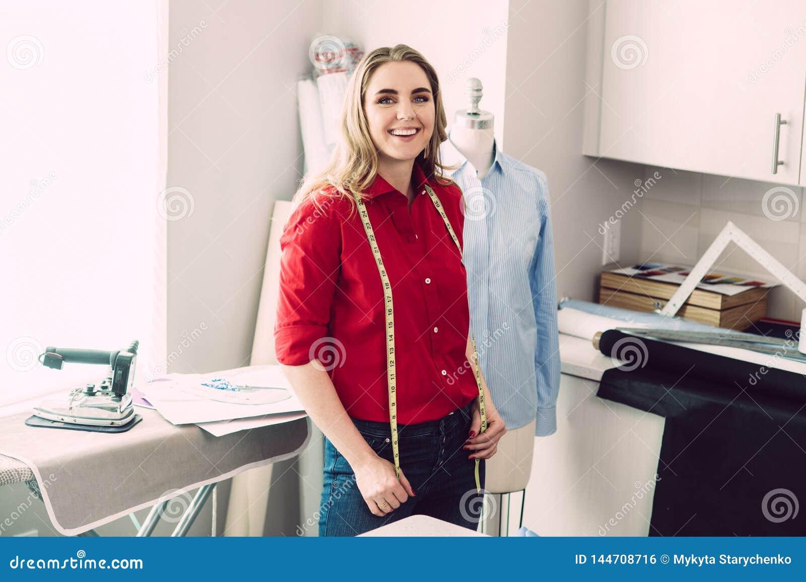 A mulher feliz do alfaiate com o manequim com linha de medição na oficina aprecia seus trabalho e negócio