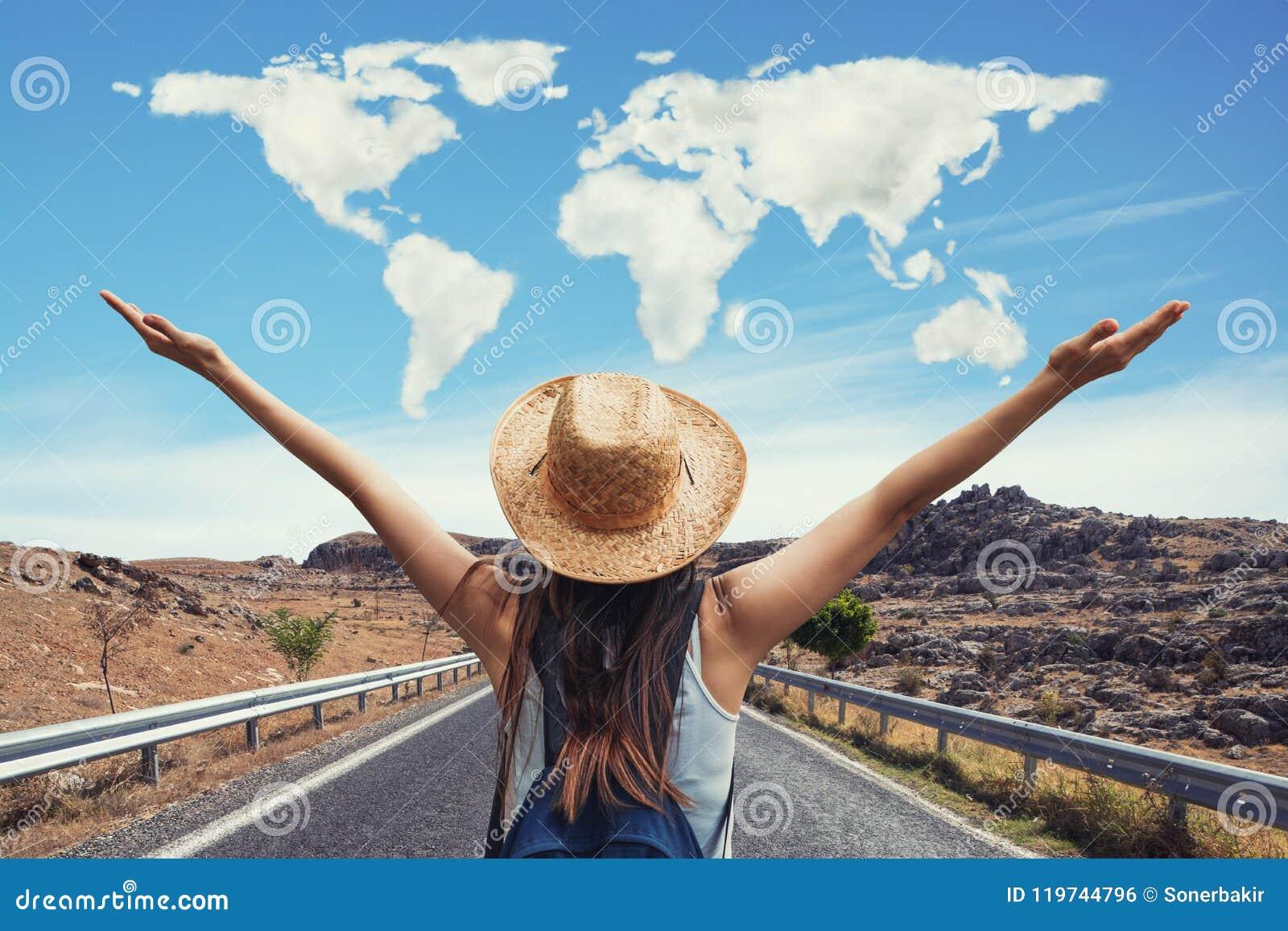 A mulher feliz do curso no conceito das férias com mundo deu forma a nuvens O viajante engraçado aprecia sua viagem e apronta-se