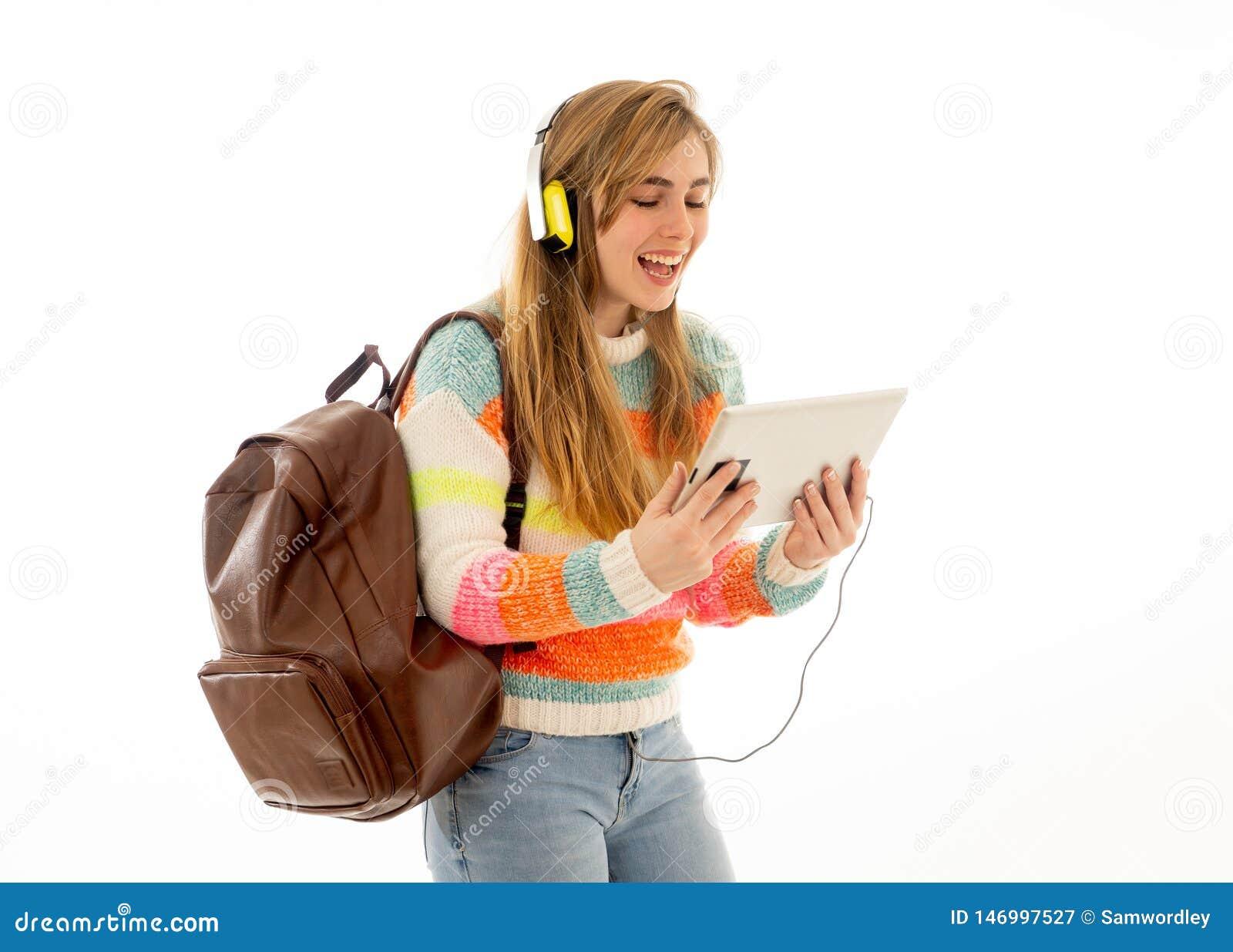 Mulher feliz do estudante nos fones de ouvido que olham a tabuleta digital que escuta a m?sica ou o curso video