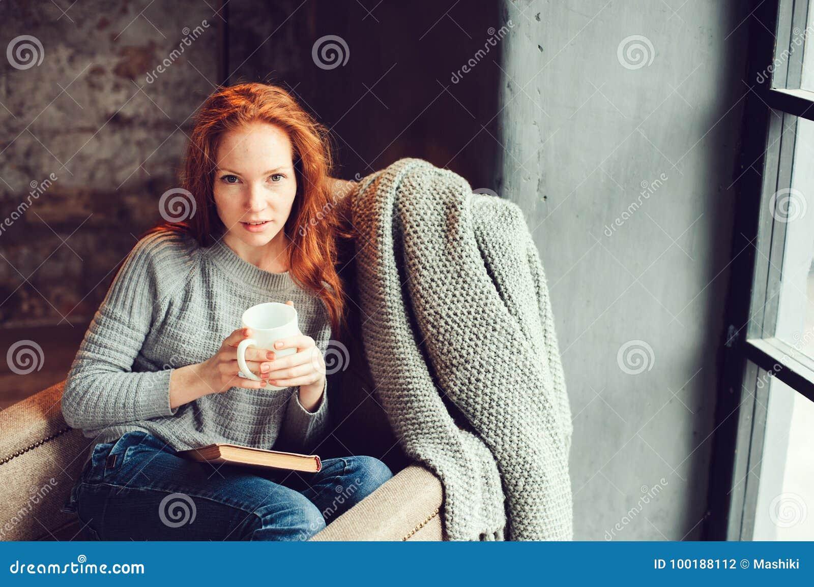 Mulher feliz do ruivo que relaxa em casa no fim de semana acolhedor do inverno ou do outono com o livro e o copo do chá quente, s
