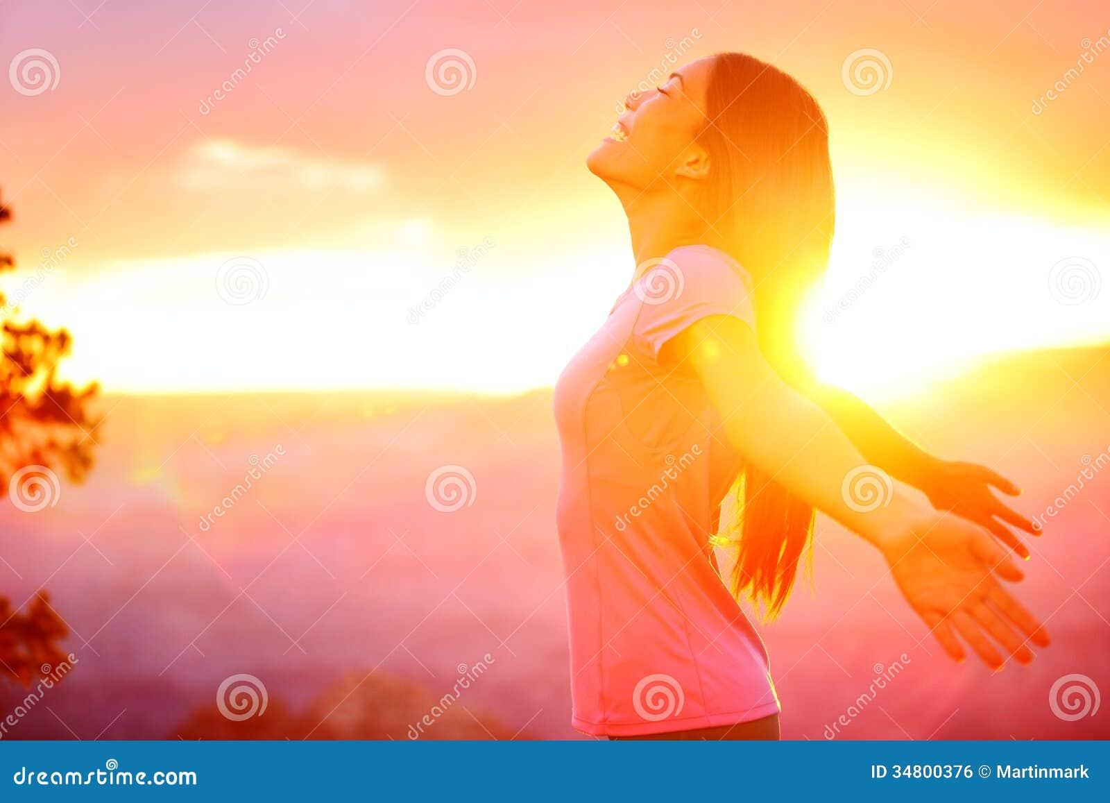Mulher feliz livre que aprecia o por do sol da natureza