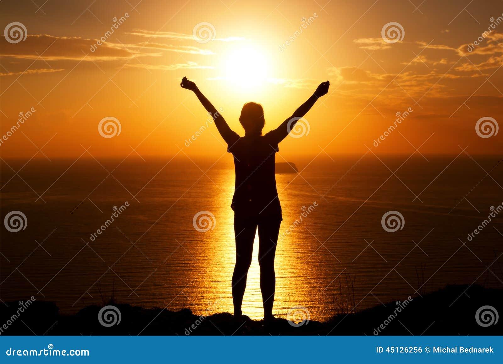 Mulher feliz na rocha com mãos acima