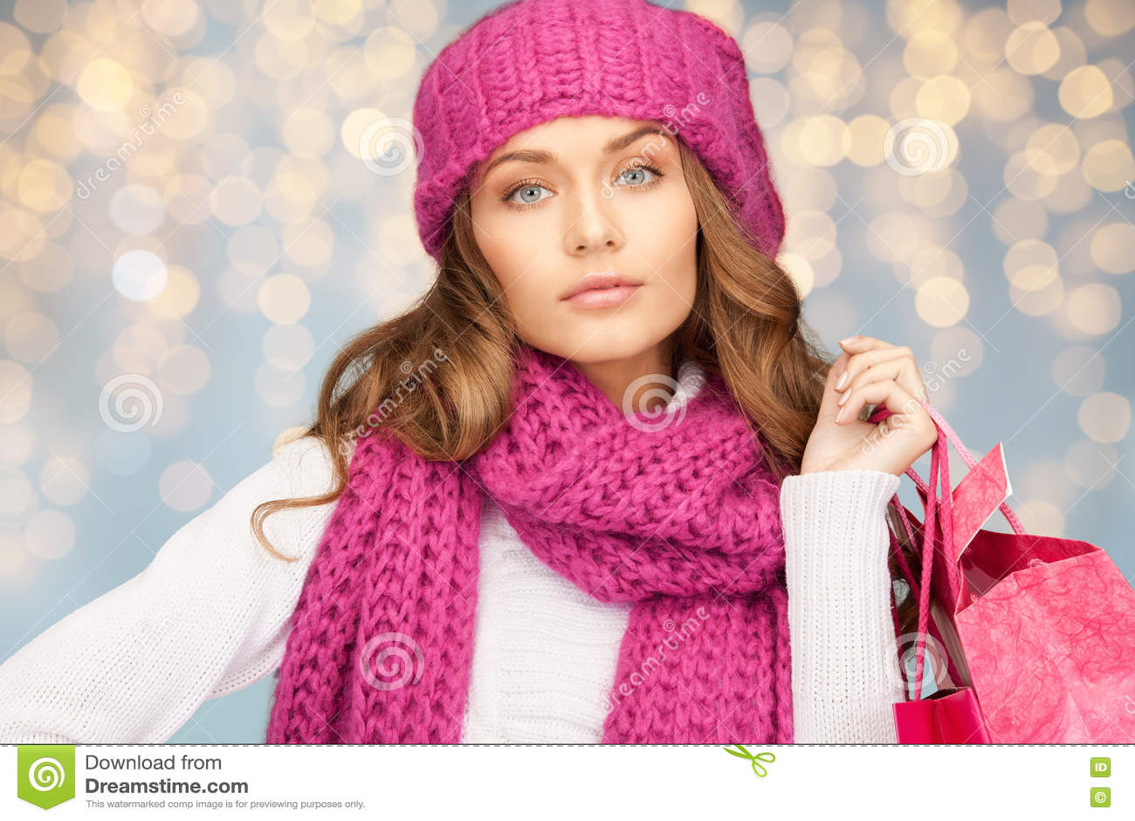 Mulher feliz na roupa do inverno com sacos de compras