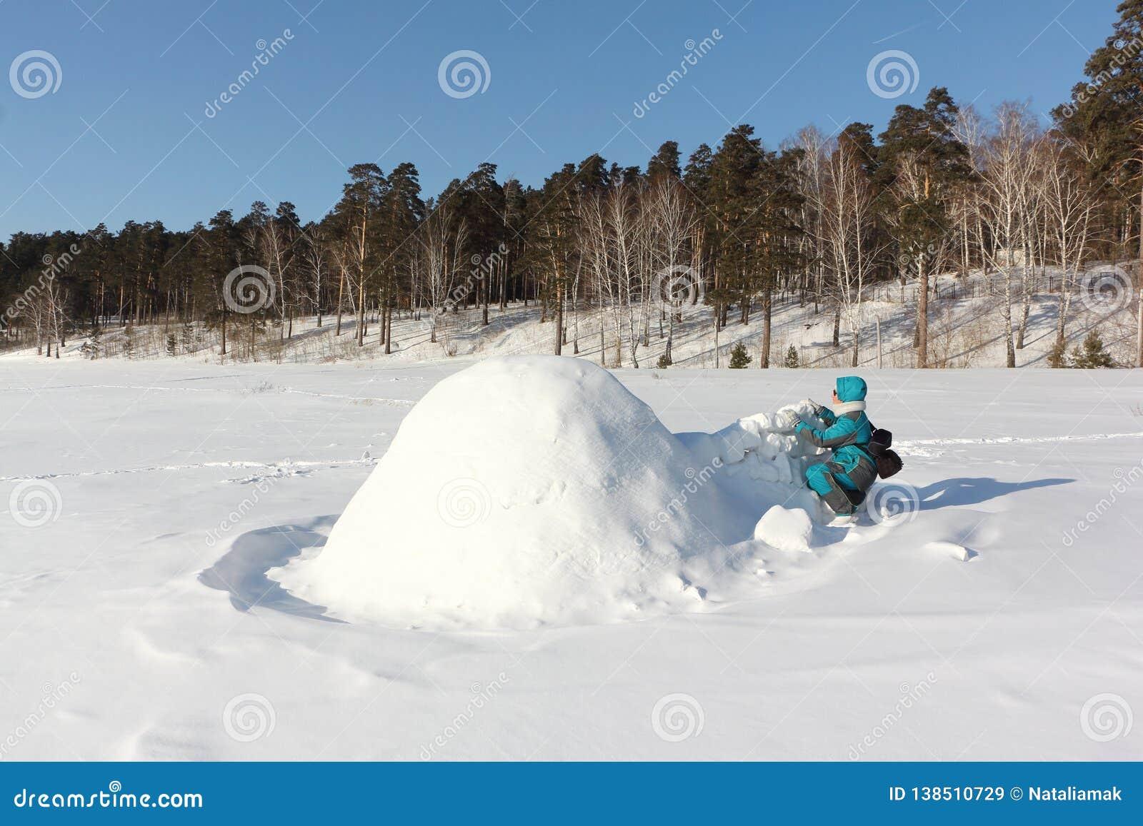 Mulher feliz na roupa morna que constrói um iglu em uma clareira no inverno, Sibéria da neve, Rússia
