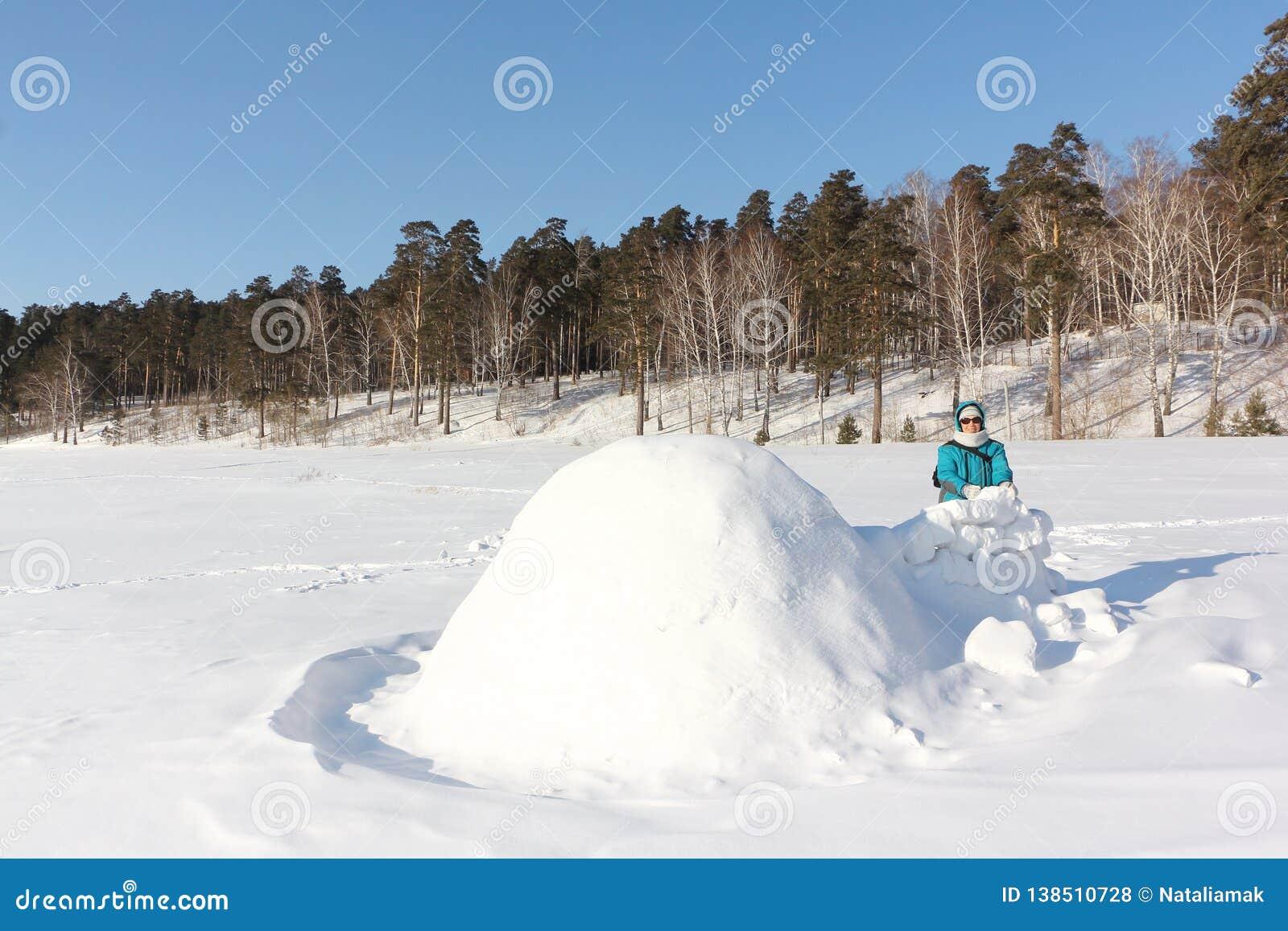 Mulher feliz na roupa morna que está perto do iglu em uma clareira no inverno, Sibéria da neve, Rússia