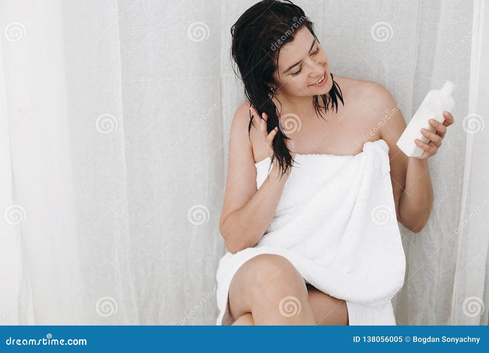 Mulher feliz nova na garrafa branca da terra arrendada de toalha do creme ou do condicionador para o cabelo no banheiro Pele, cor