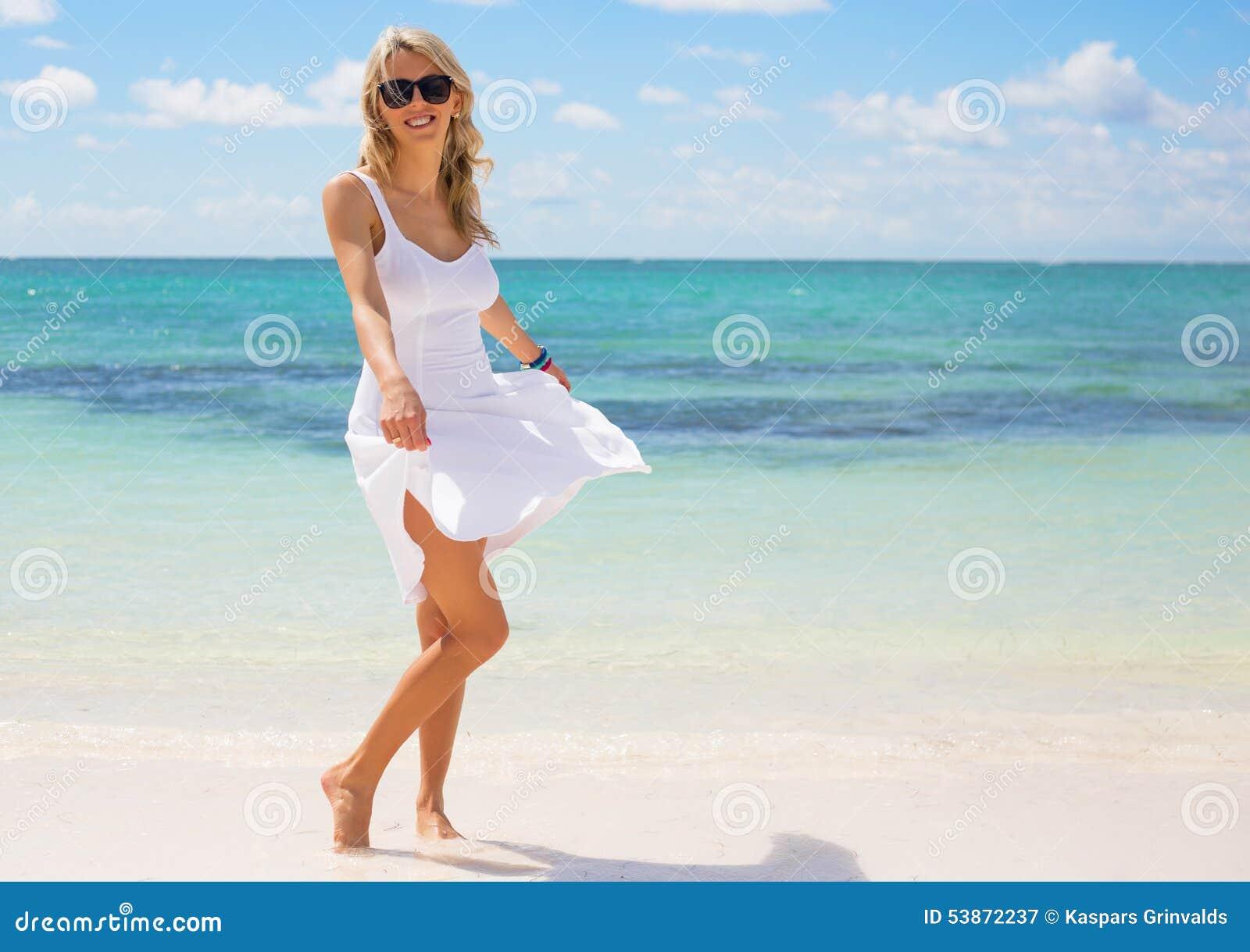 Mulher feliz nova no vestido branco na praia
