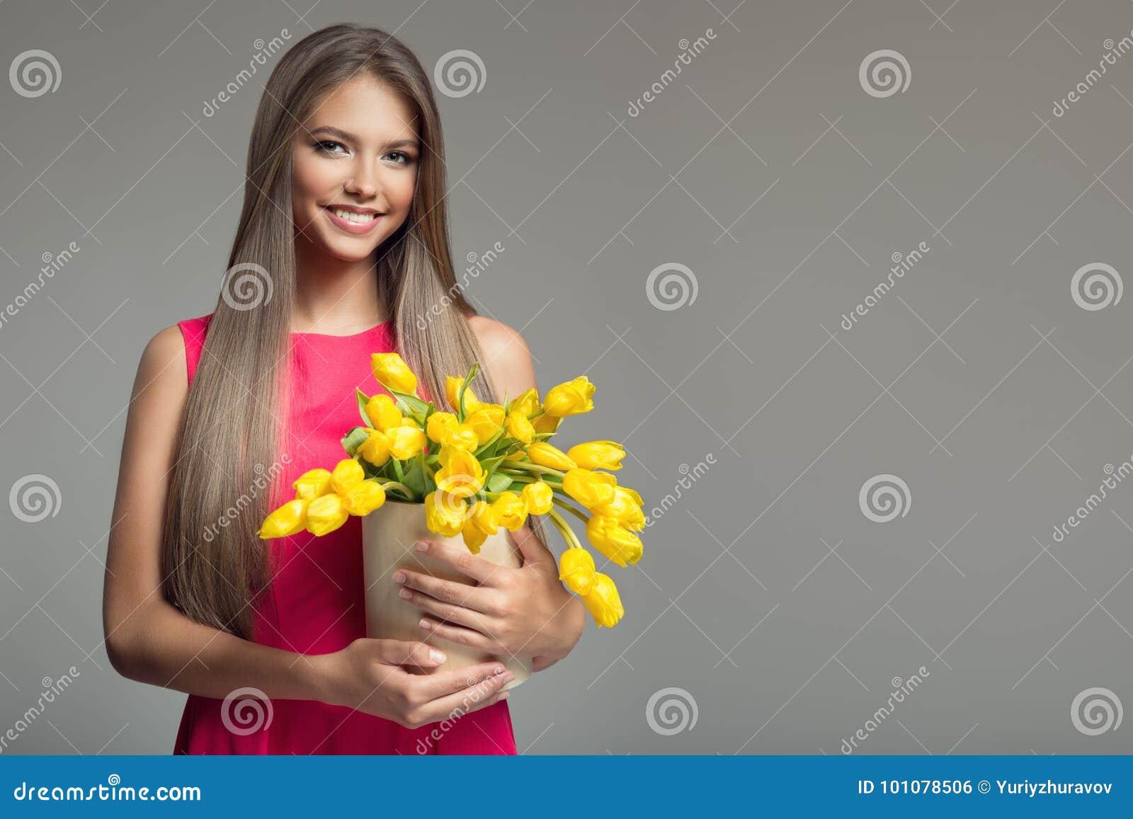 Mulher feliz nova que guarda a cesta com tulipas amarelas Backgr cinzento