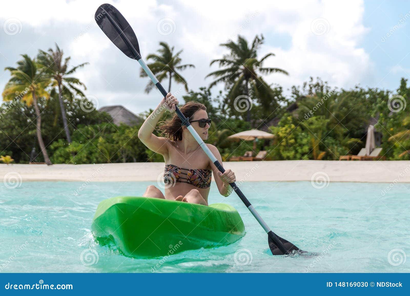 Mulher feliz nova que kayaking em uma ilha tropical em Maldivas ?gua azul desobstru?da