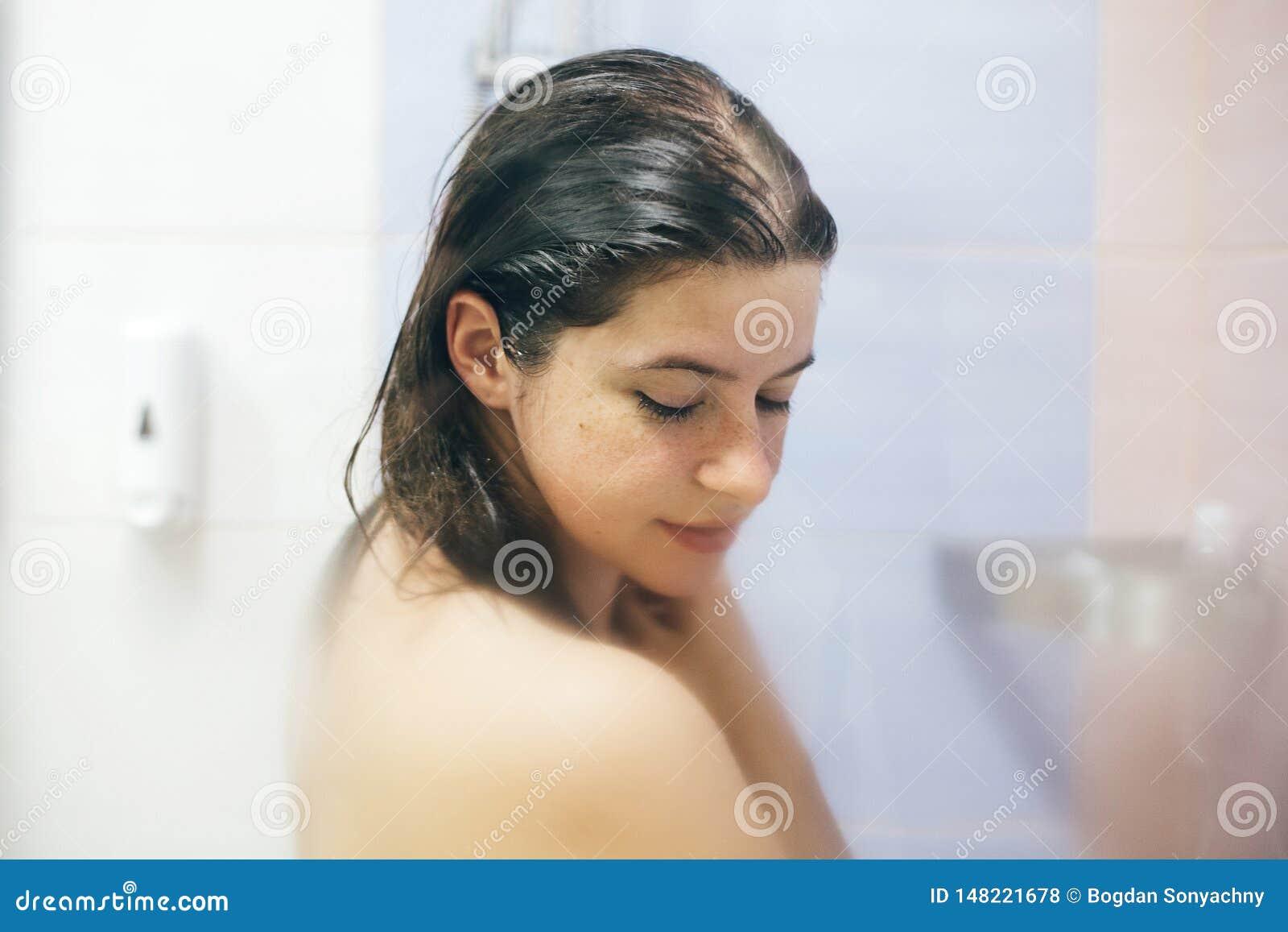 Mulher feliz nova que toma o chuveiro em casa ou o banheiro do hotel A menina moreno bonita que lava seu cabelo e que aprecia rel