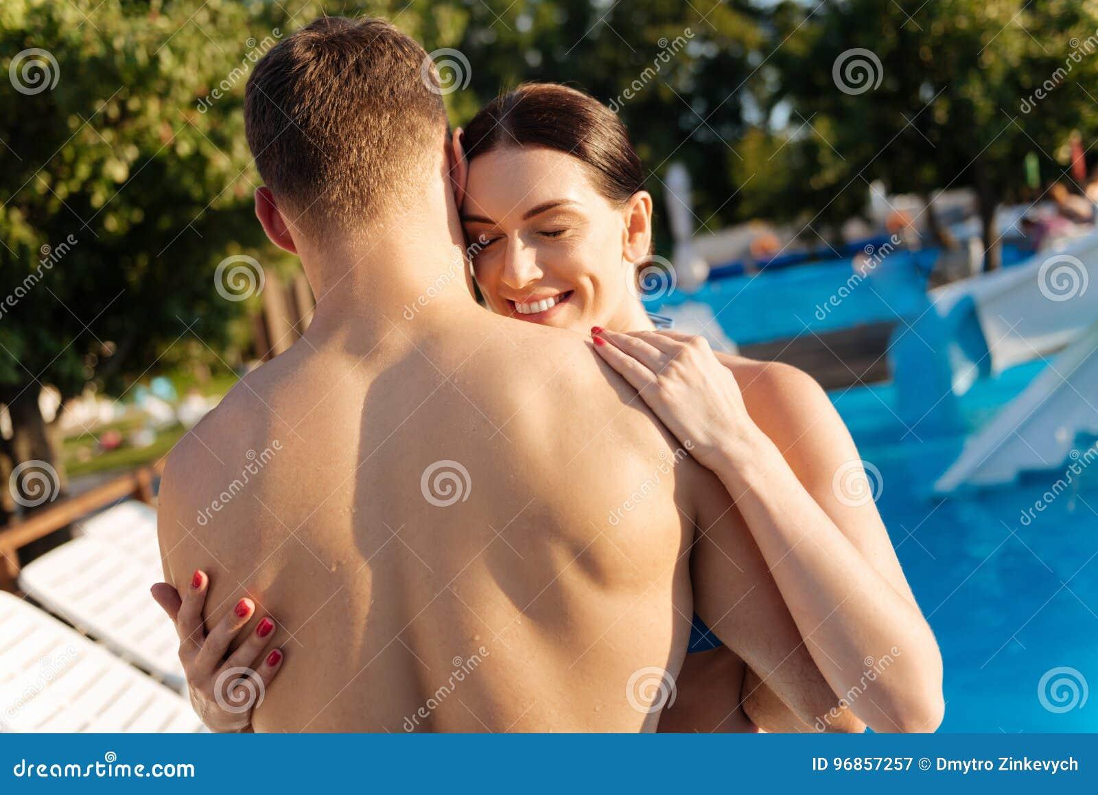 Mulher feliz que abraça seu marido no recurso