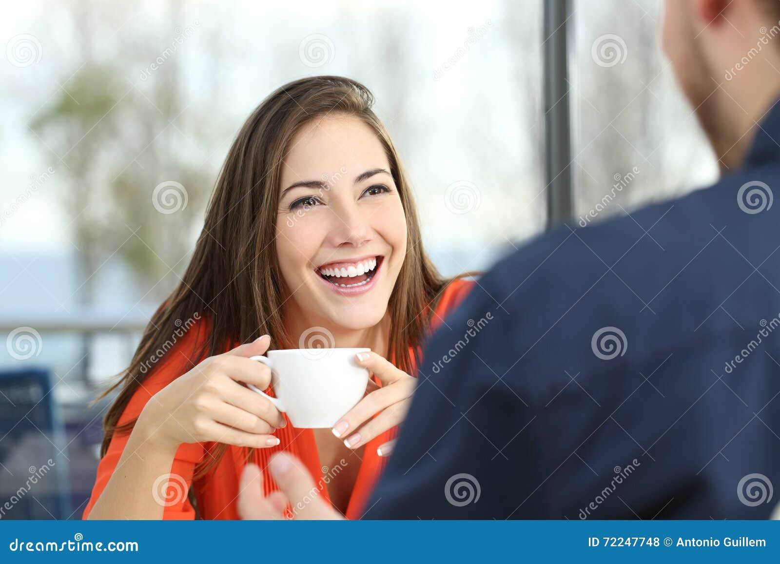 Mulher feliz que data em uma cafetaria