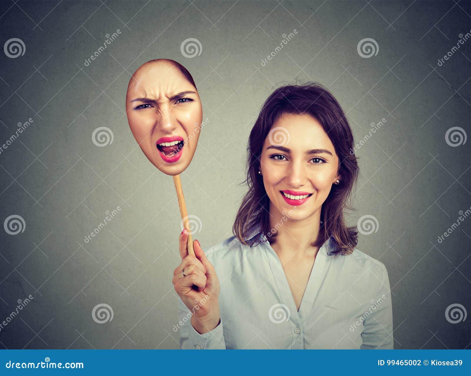 Mulher feliz que descola uma máscara irritada dsi mesma