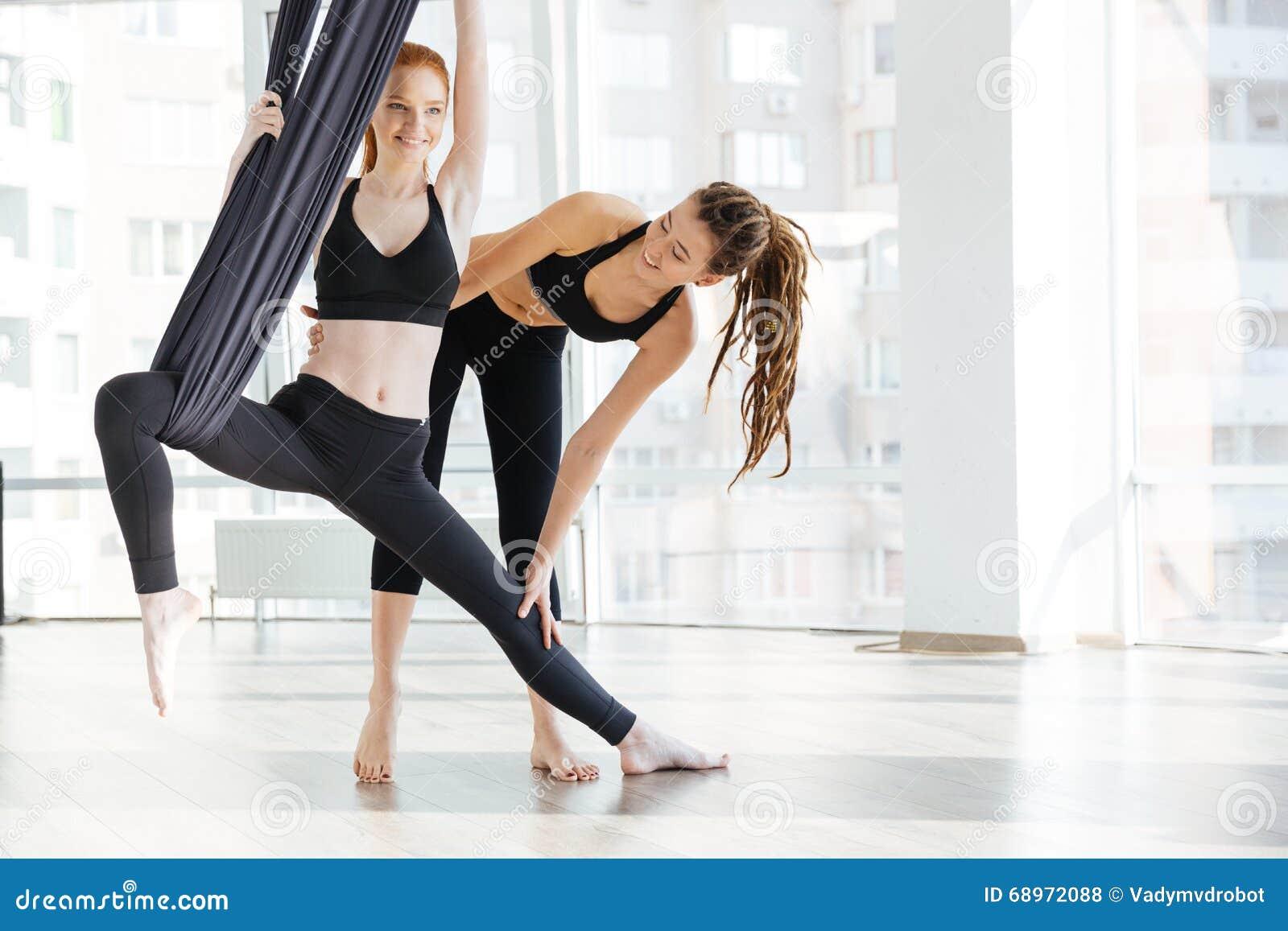 Mulher feliz que faz a ioga aérea com o instrutor no estúdio