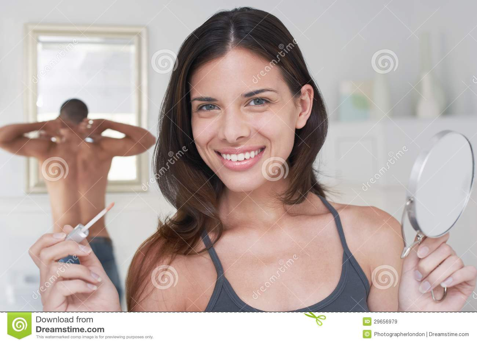Mulher feliz que guardara o aplicador e o espelho