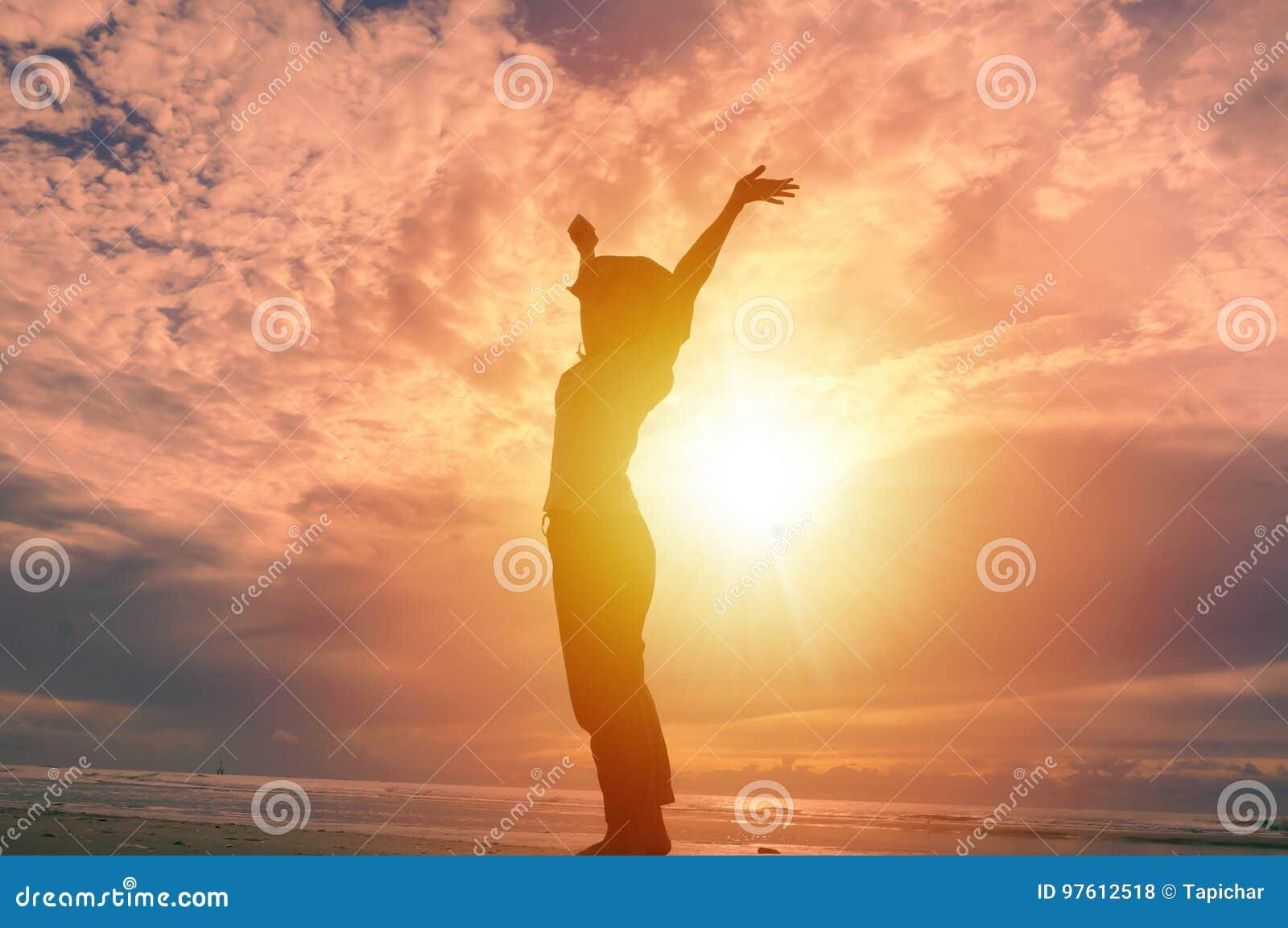 Mulher feliz que levanta as mãos acima e o nascer do sol bonito no fundo
