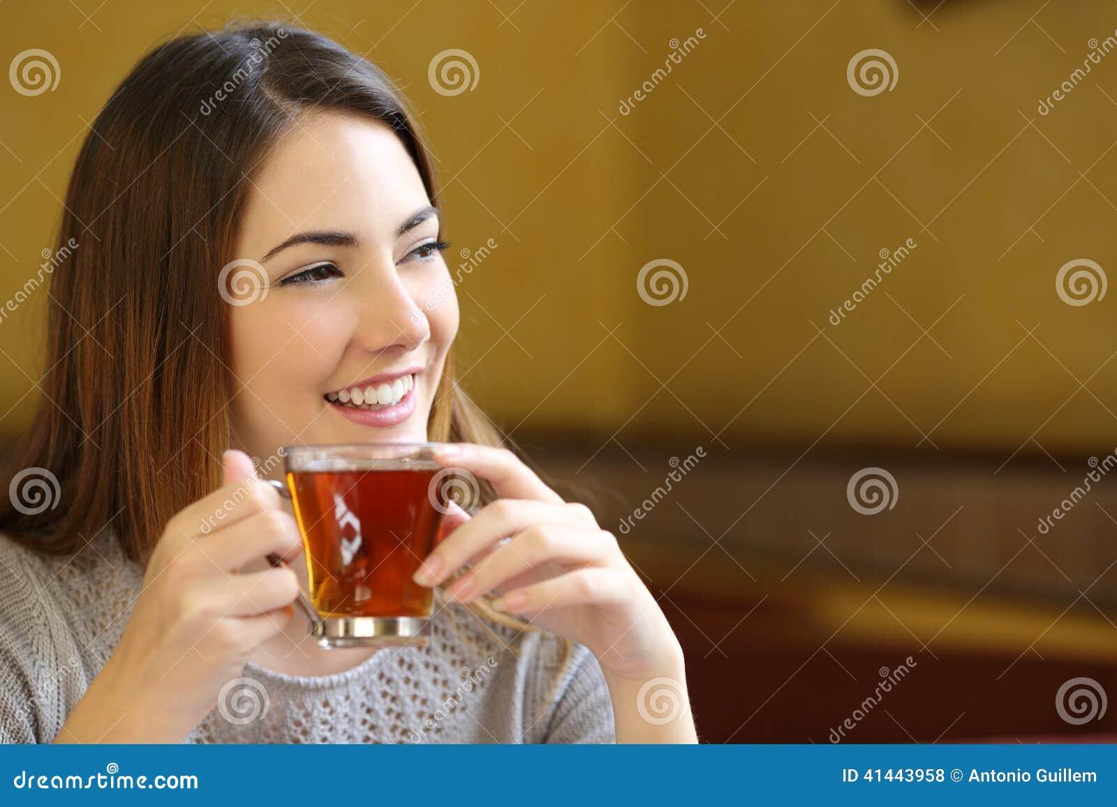 Mulher feliz que pensa guardando um copo do chá em uma cafetaria