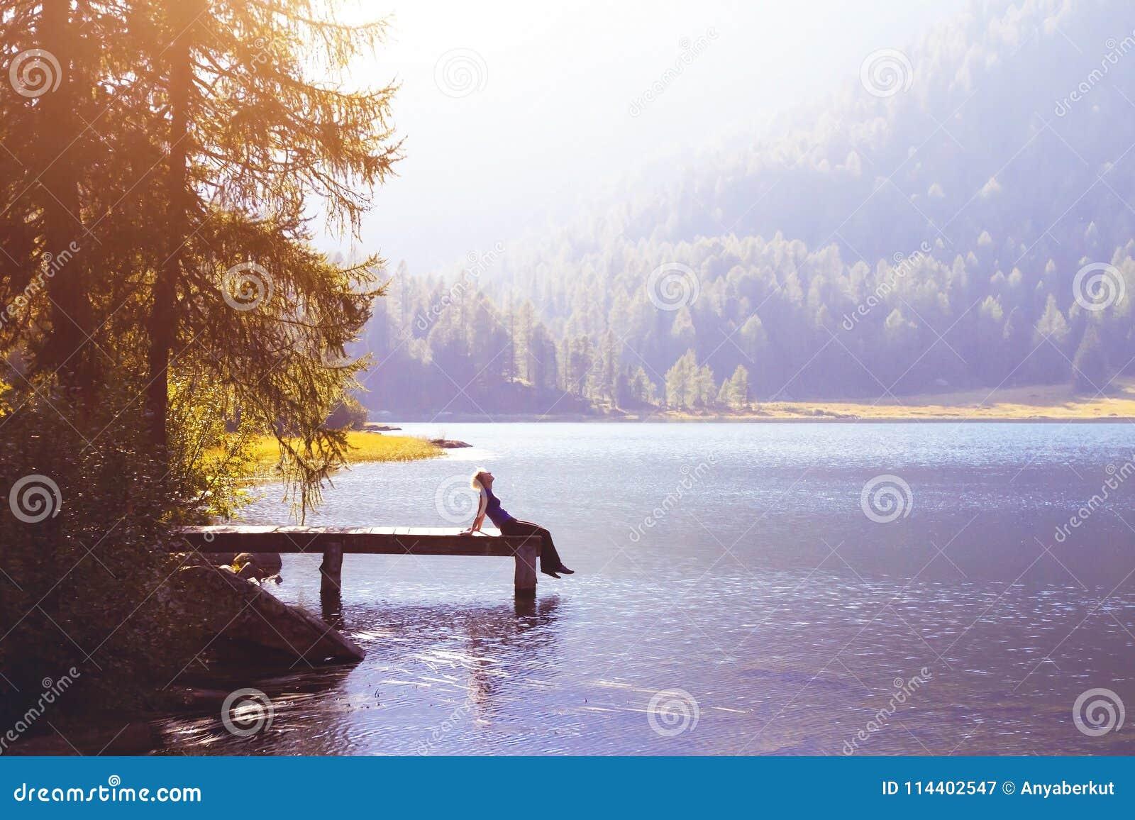 Mulher feliz que senta-se no conceito do cais e do sorriso, da felicidade ou da inspiração