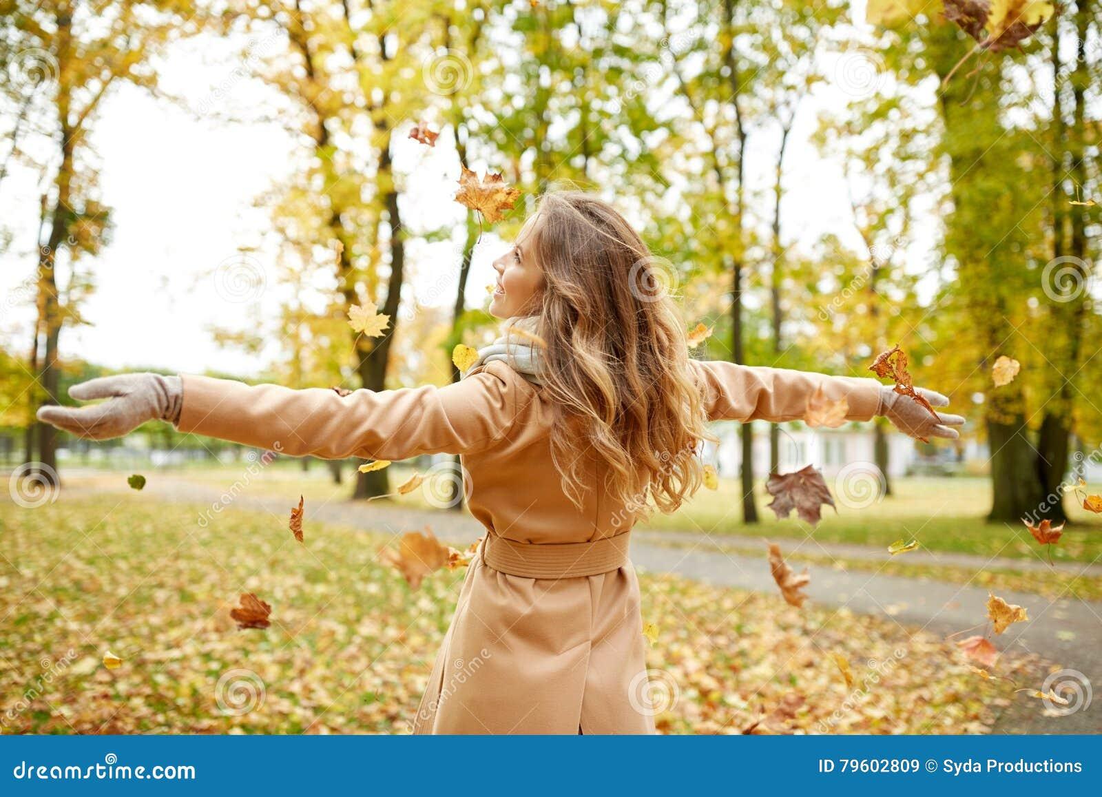 Mulher feliz que tem o divertimento com as folhas no parque do outono