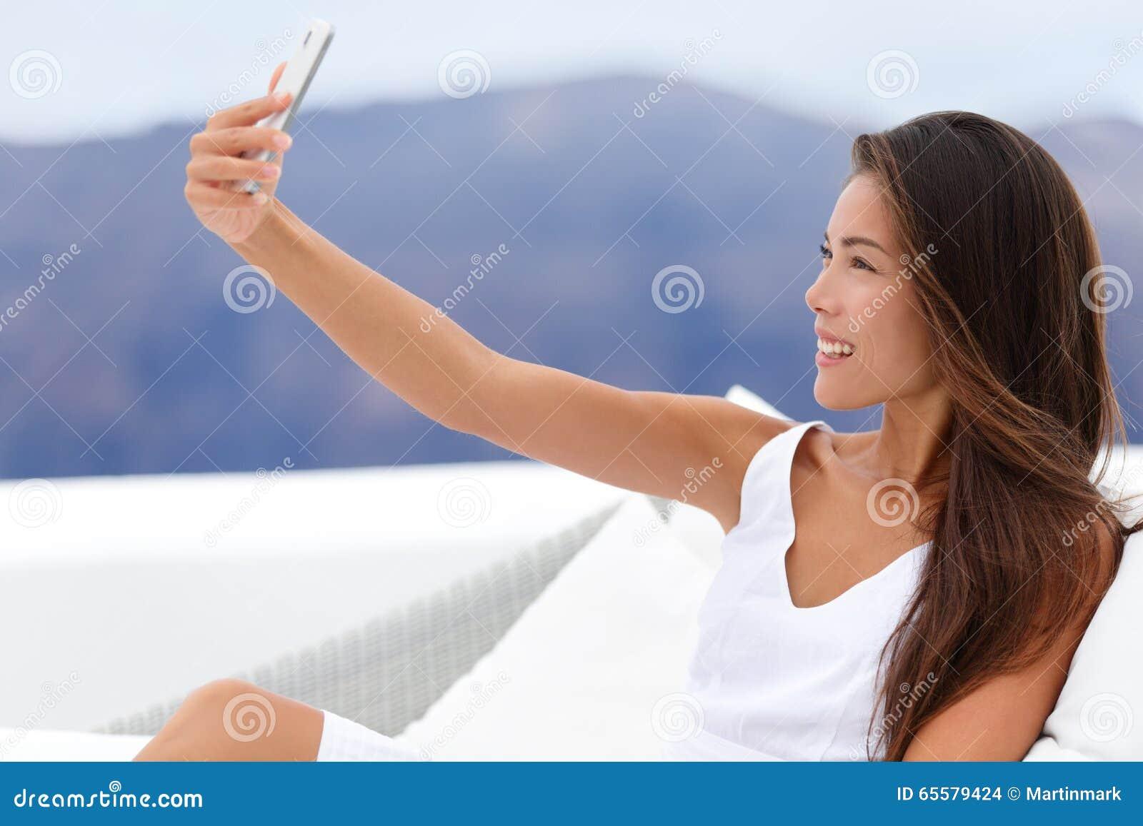 Mulher feliz que toma Selfie em Sofa Outside