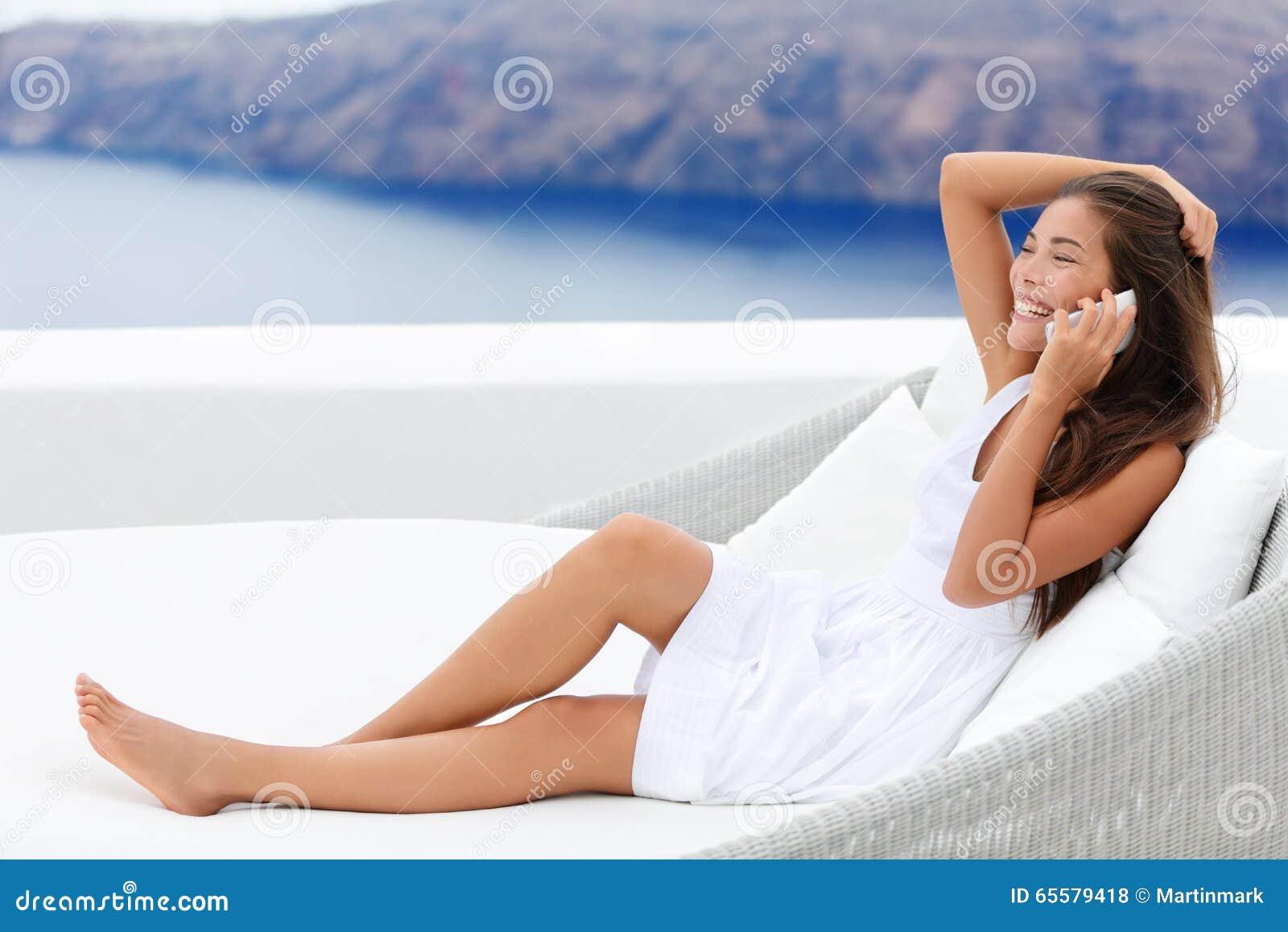 Mulher feliz que usa Smartphone no sofá no recurso