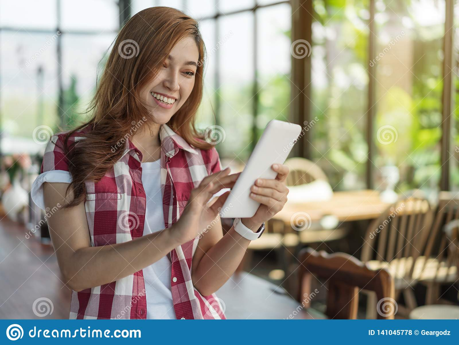 Mulher feliz que usa a tabuleta digital no café
