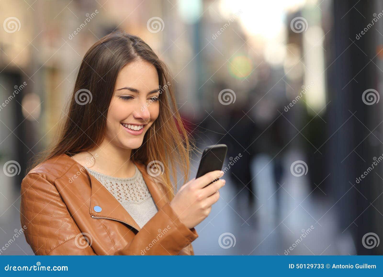 Mulher feliz que usa um telefone esperto na rua