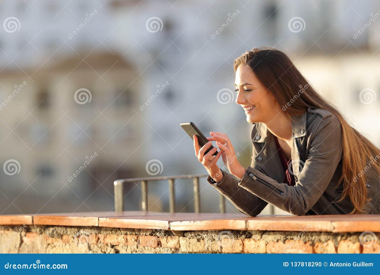 A mulher feliz usa um telefone esperto em um balcão no por do sol