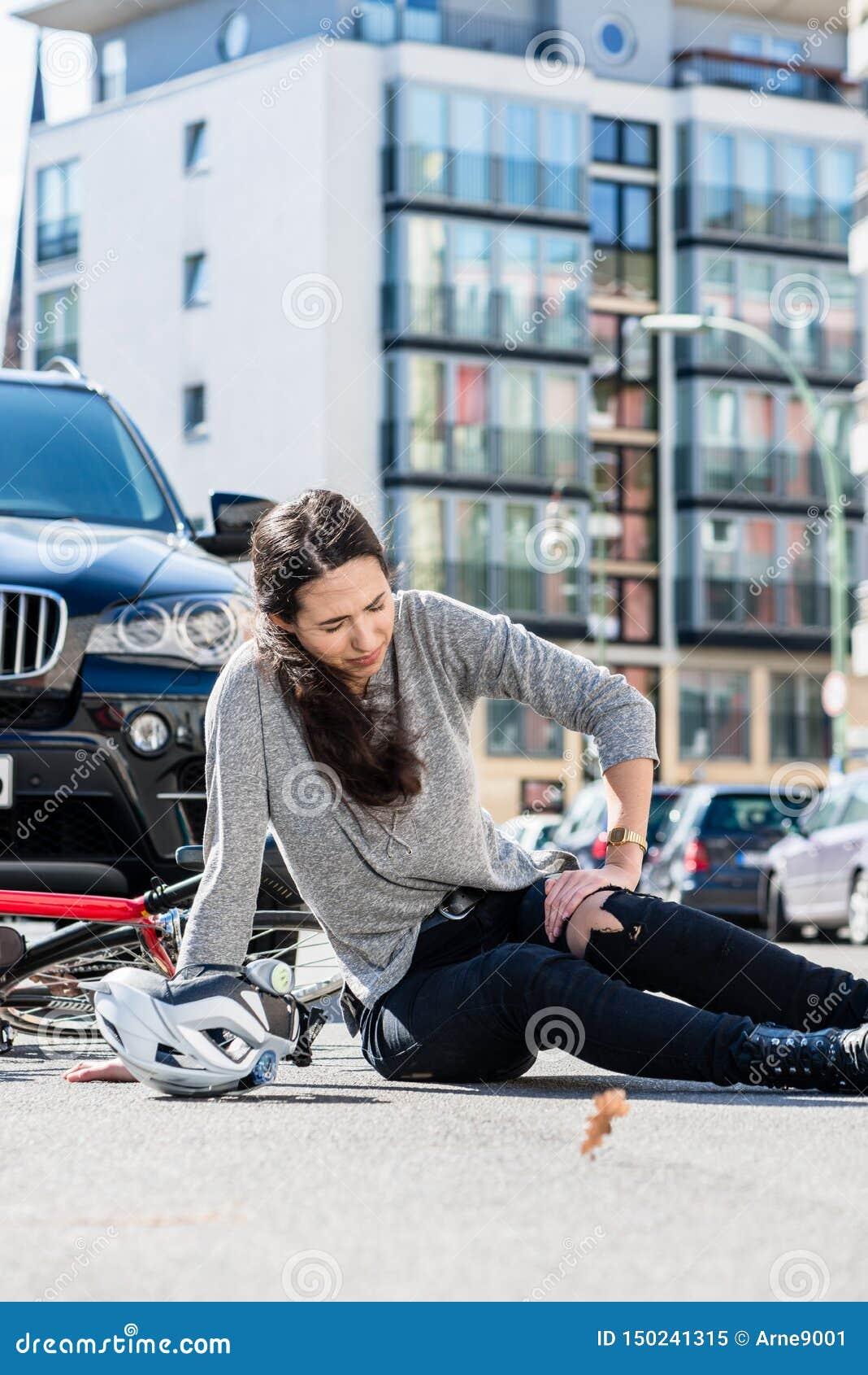 Mulher ferida com a dor severa causada pela entorse do joelho após o acidente da bicicleta