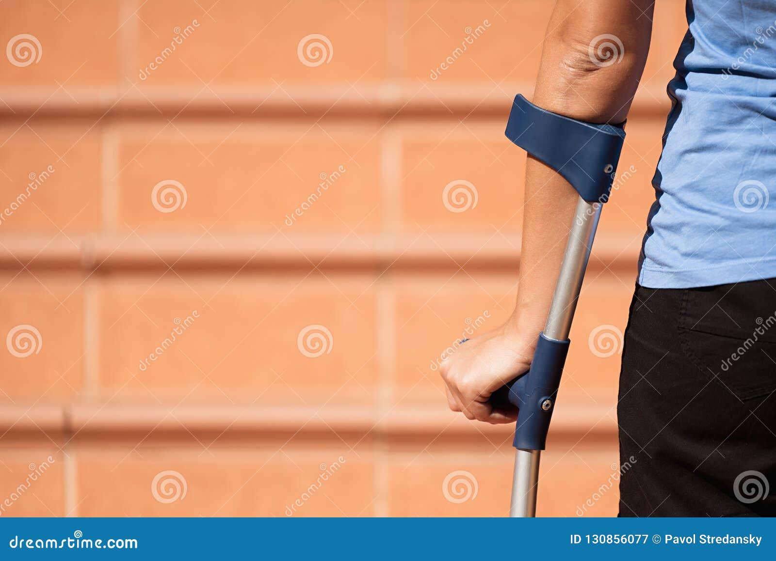 Mulher ferida que tenta andar em muletas