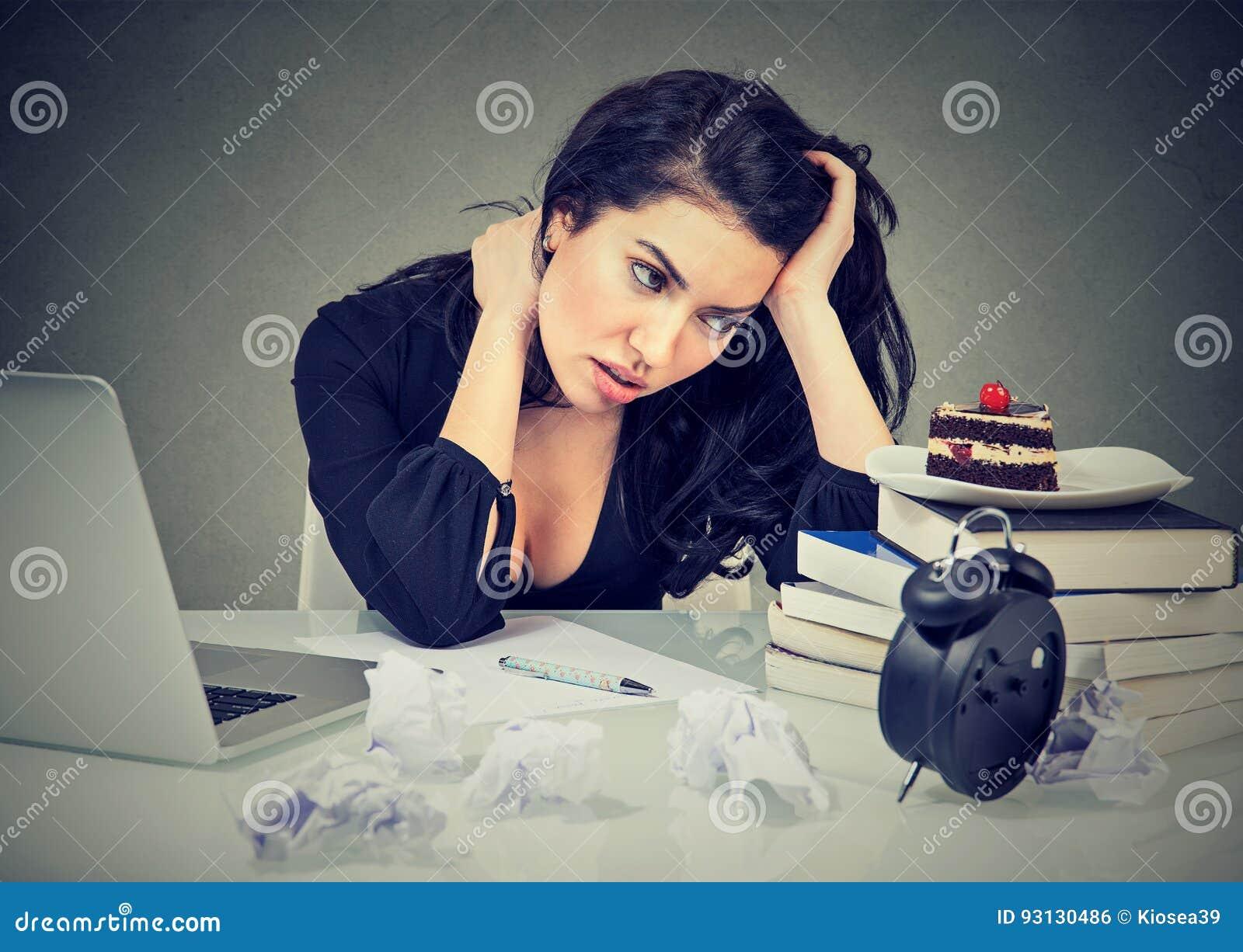 A mulher forçada que senta-se na mesa em seu escritório sobrecarregou o bolo doce implorando