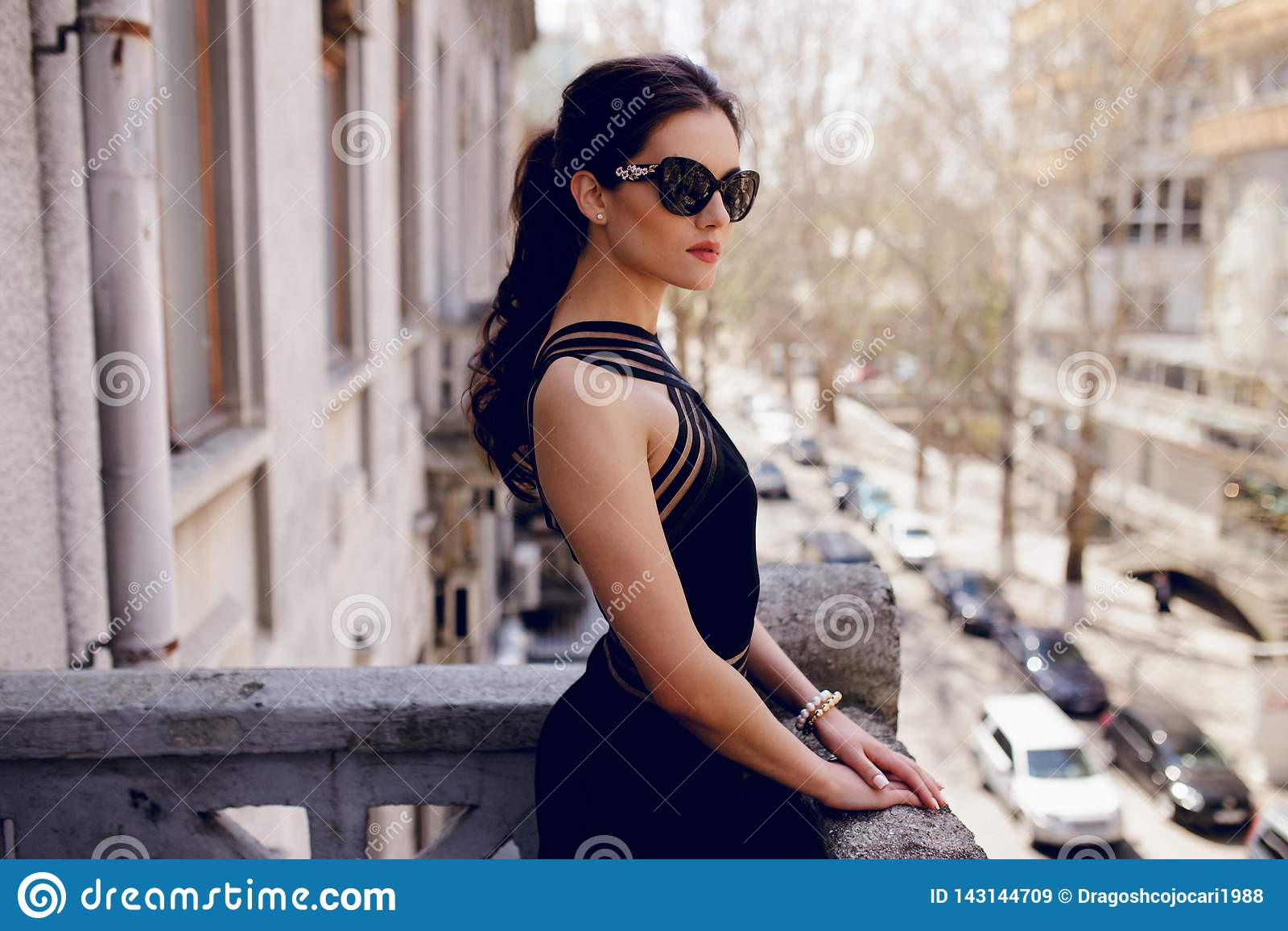 A mulher forte, elegante em óculos de sol pretos, vestido preto  sexy , rabo de cavalo do cabelo, olha com atitude no balcão