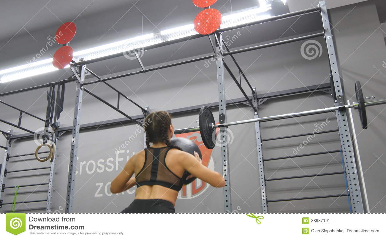 Mulher forte nova com o corpo perfeito da aptidão no sportswear que exercita com a bola de medicina no gym Menina que faz o cross