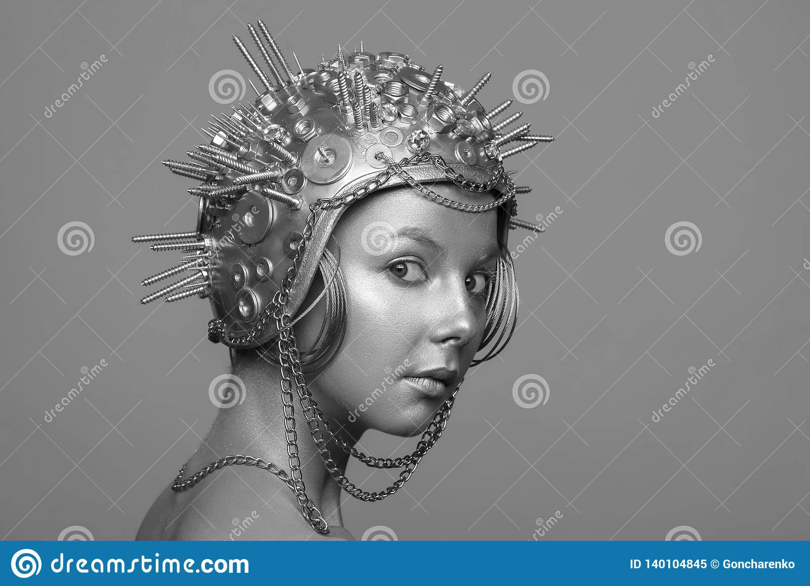 Mulher futurista no capacete do metal com parafusos, porcas e correntes