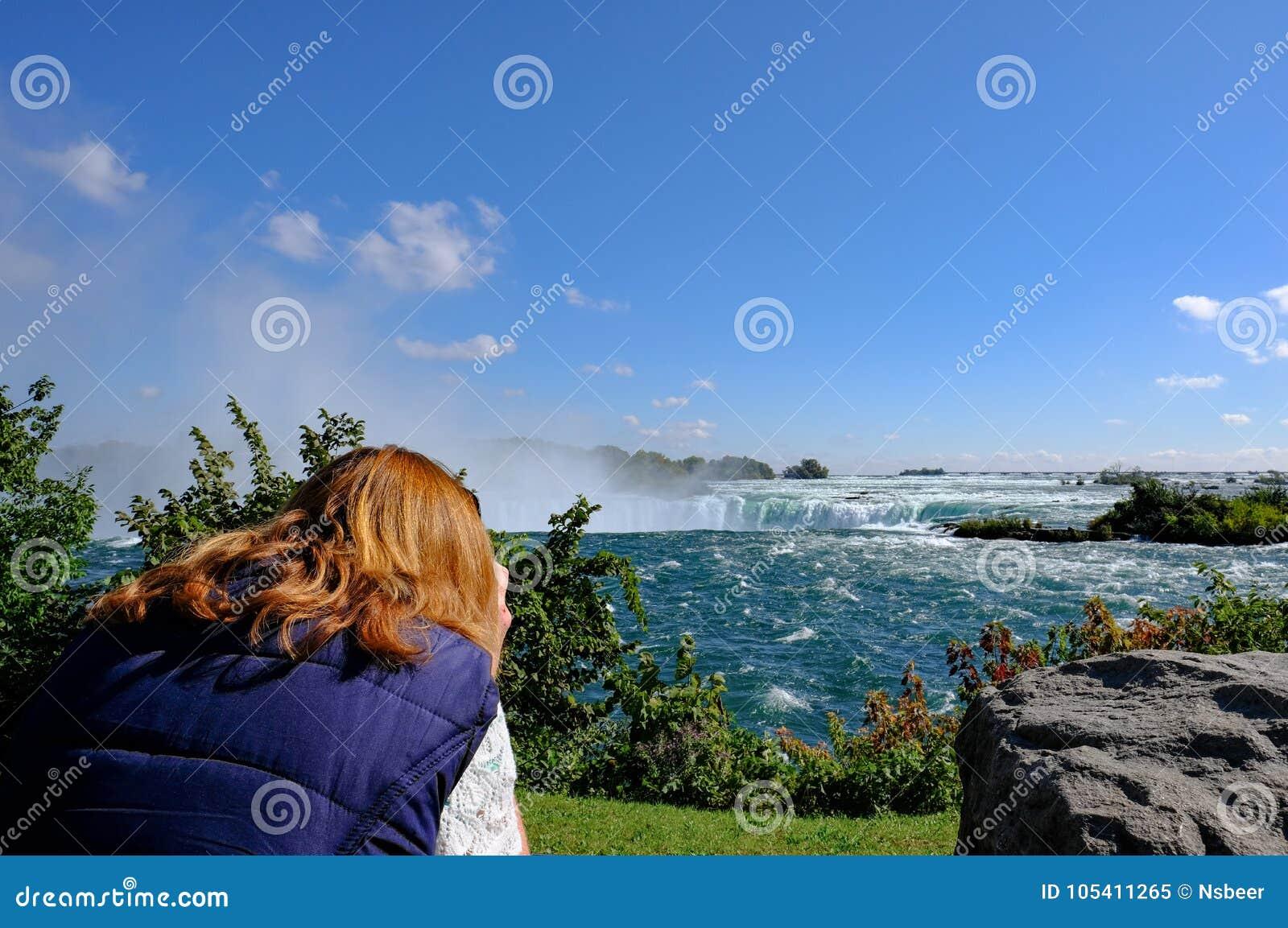 Mulher Gengibre-de cabelo vista apontar sua câmera no Niagara Falls famoso, Ontário, Canadá