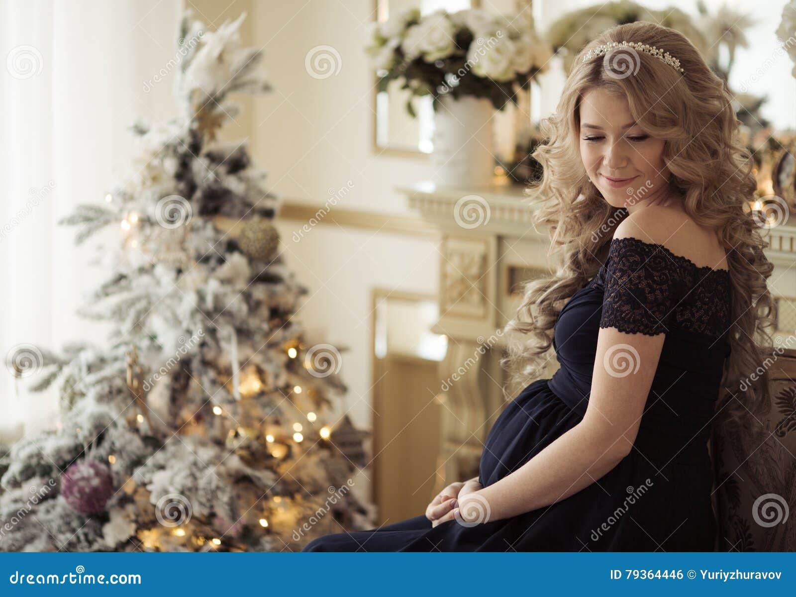 Mulher gravida bonita em um vestido do feriado