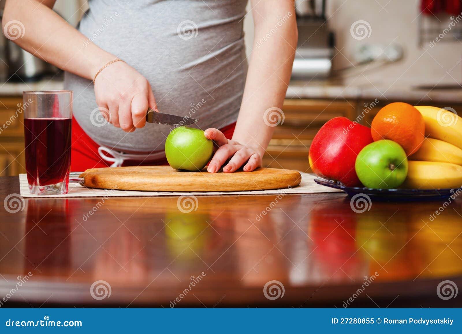 Mulher gravida bonita na cozinha