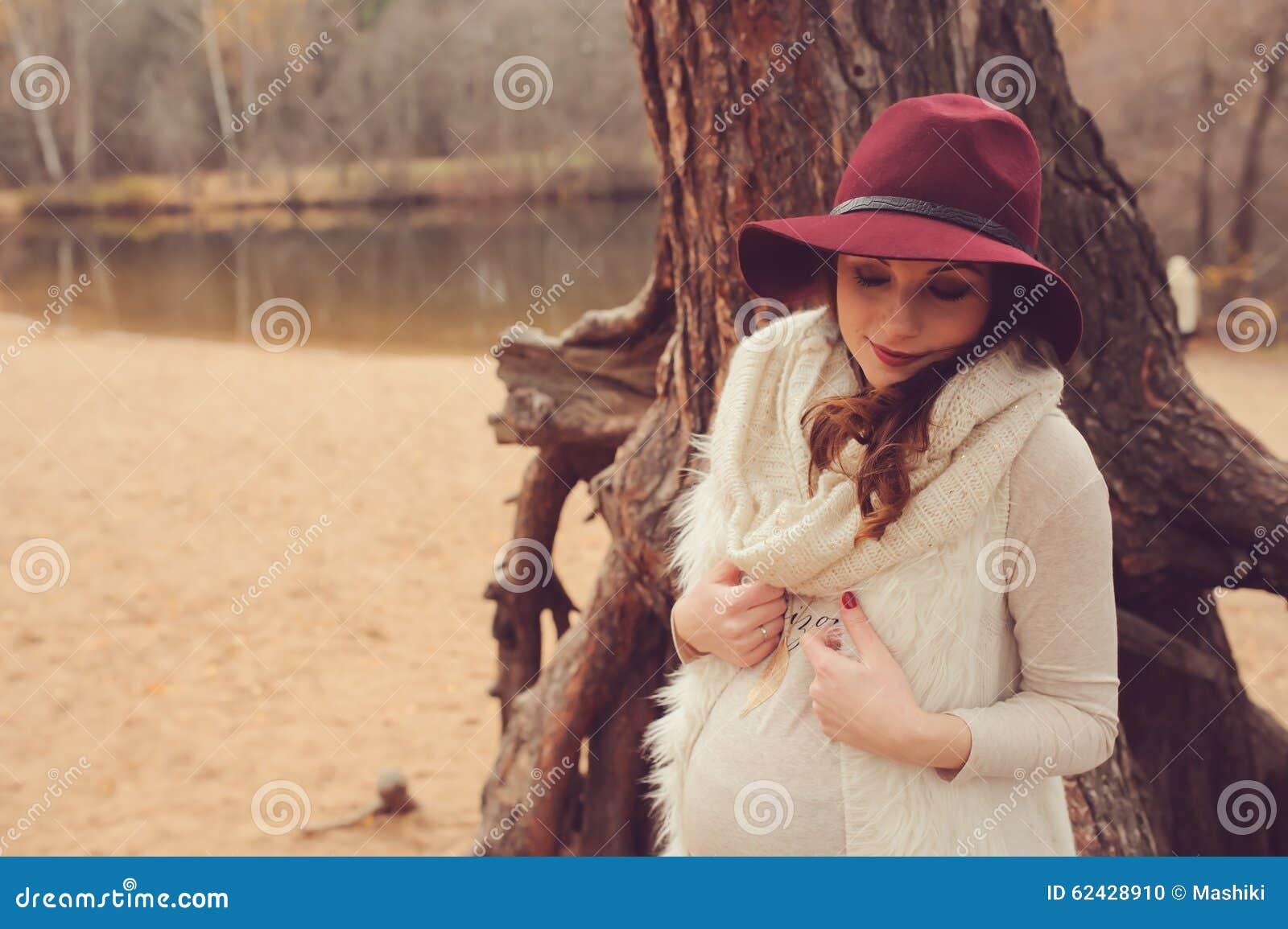 Mulher gravida bonita no chapéu da forma na caminhada exterior morna acolhedor