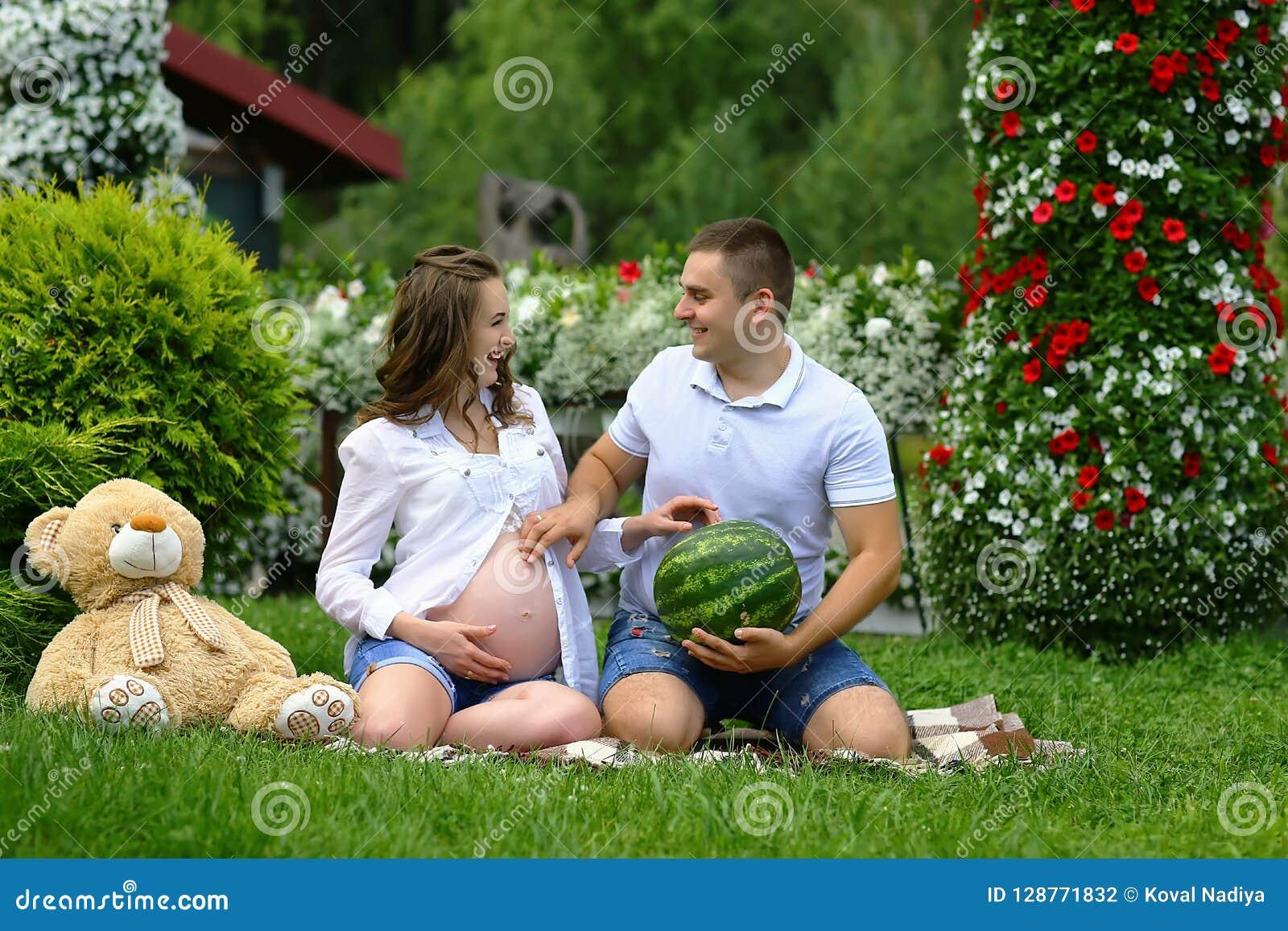 Mulher gravida engraçada que sorri junto com seu marido no parque com o urso da melancia e do luxuoso O conceito de uma vida nova