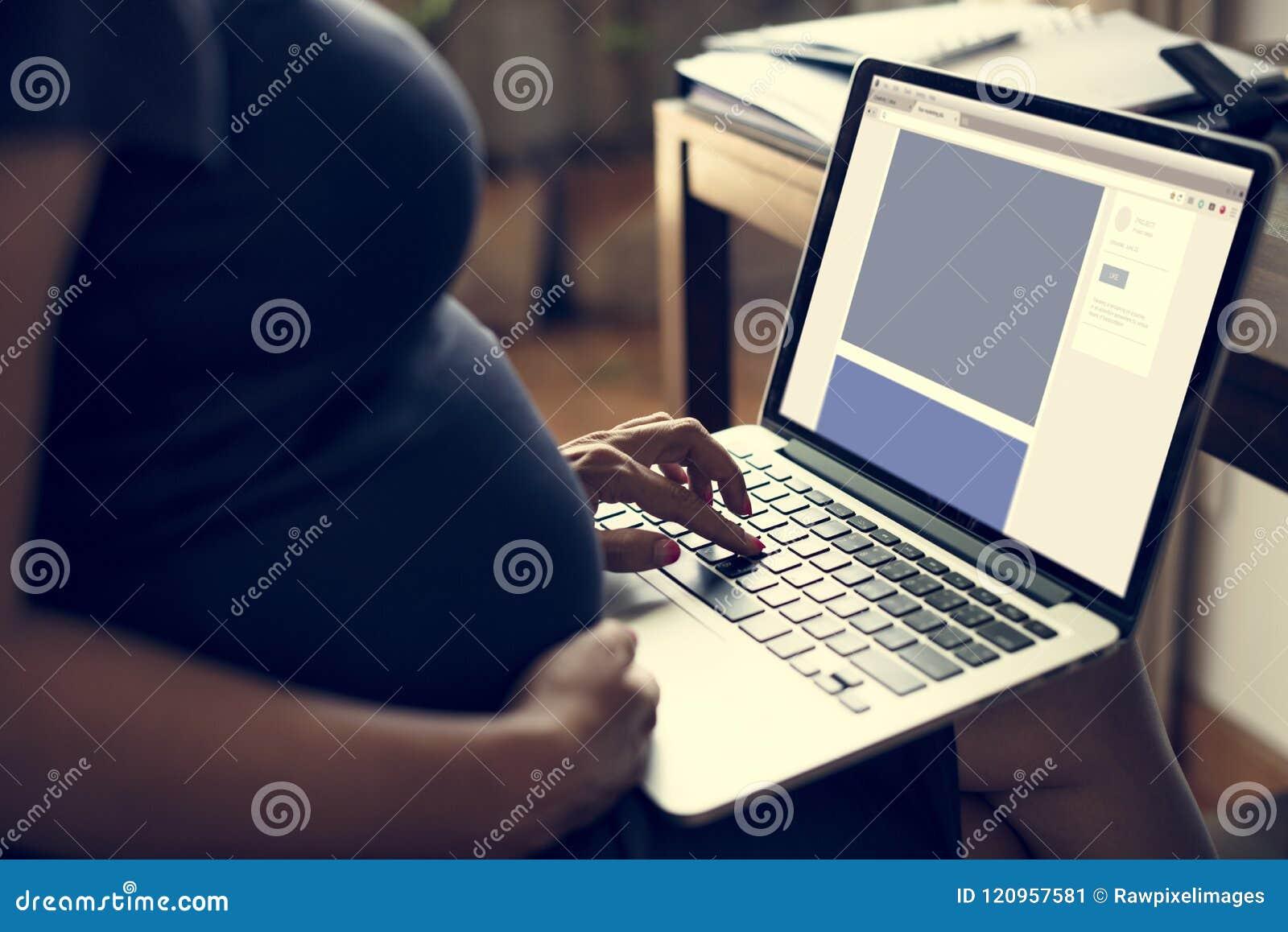 A mulher gravida está usando o portátil do computador