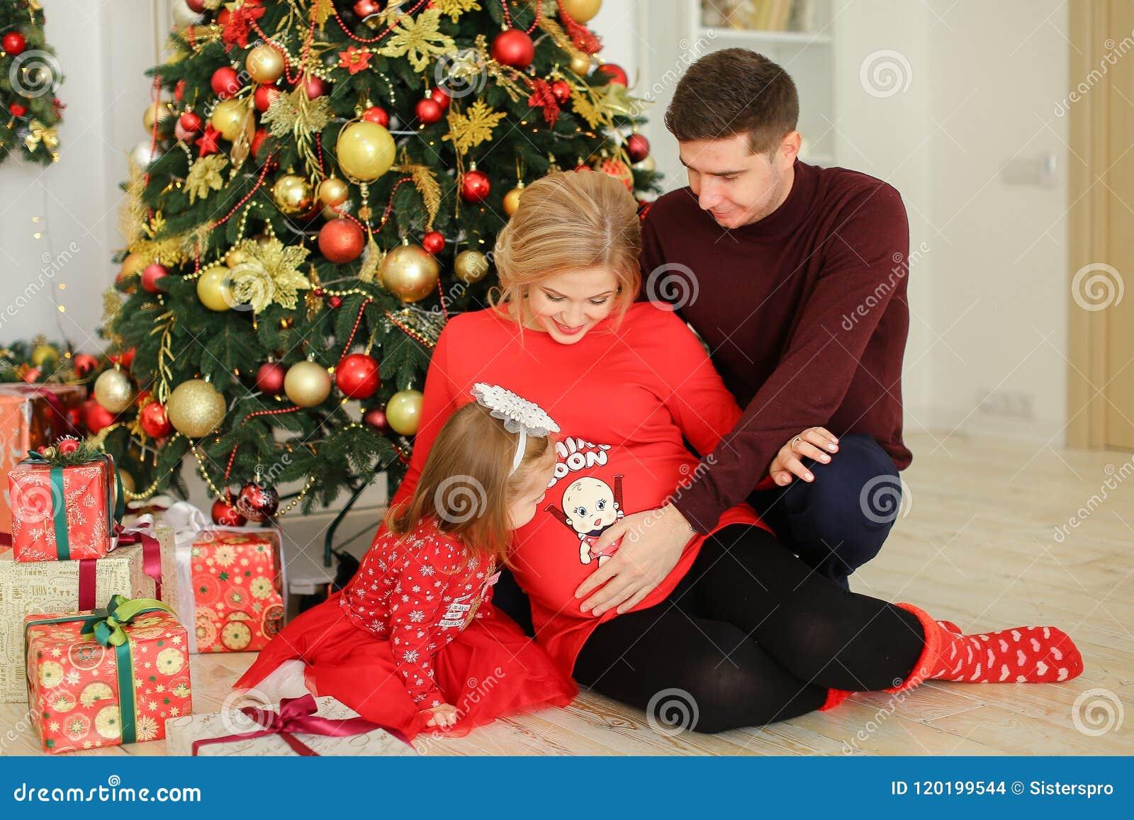 Mulher gravida europeia que senta-se com o marido que abraça a barriga e a filha pequena perto dos presentes sob a árvore de Chis