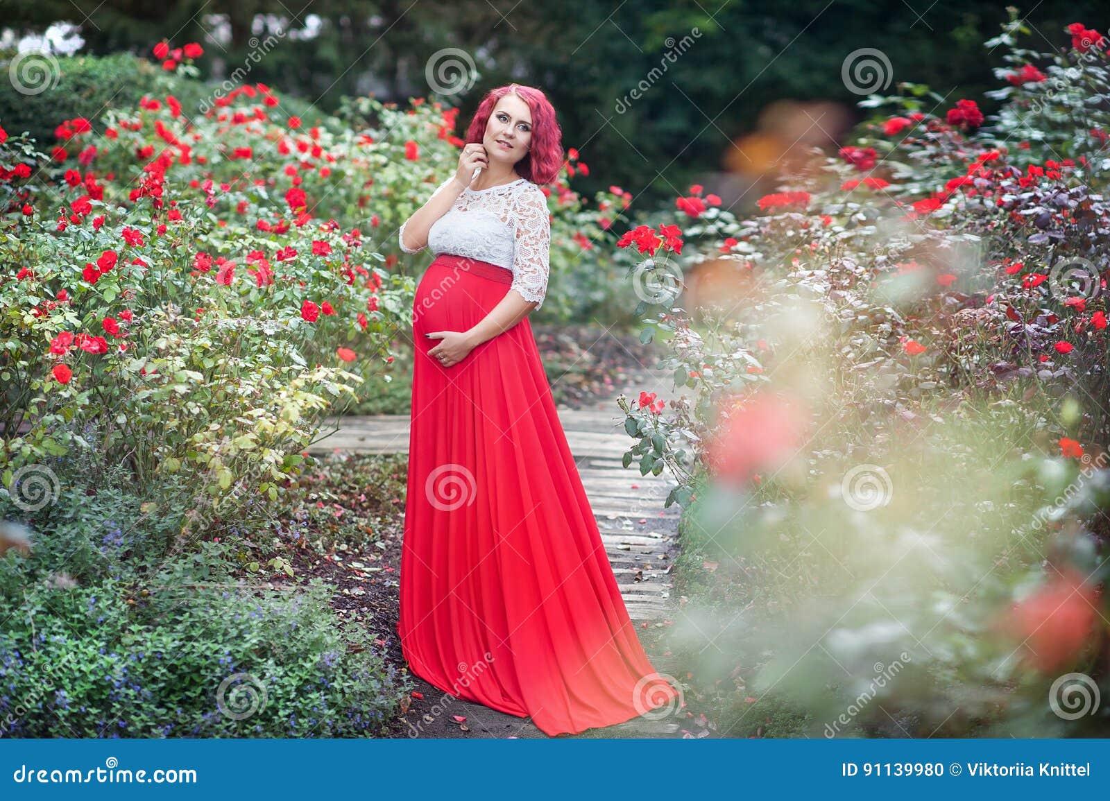 Mulher gravida nova bonita que anda no campo das rosas