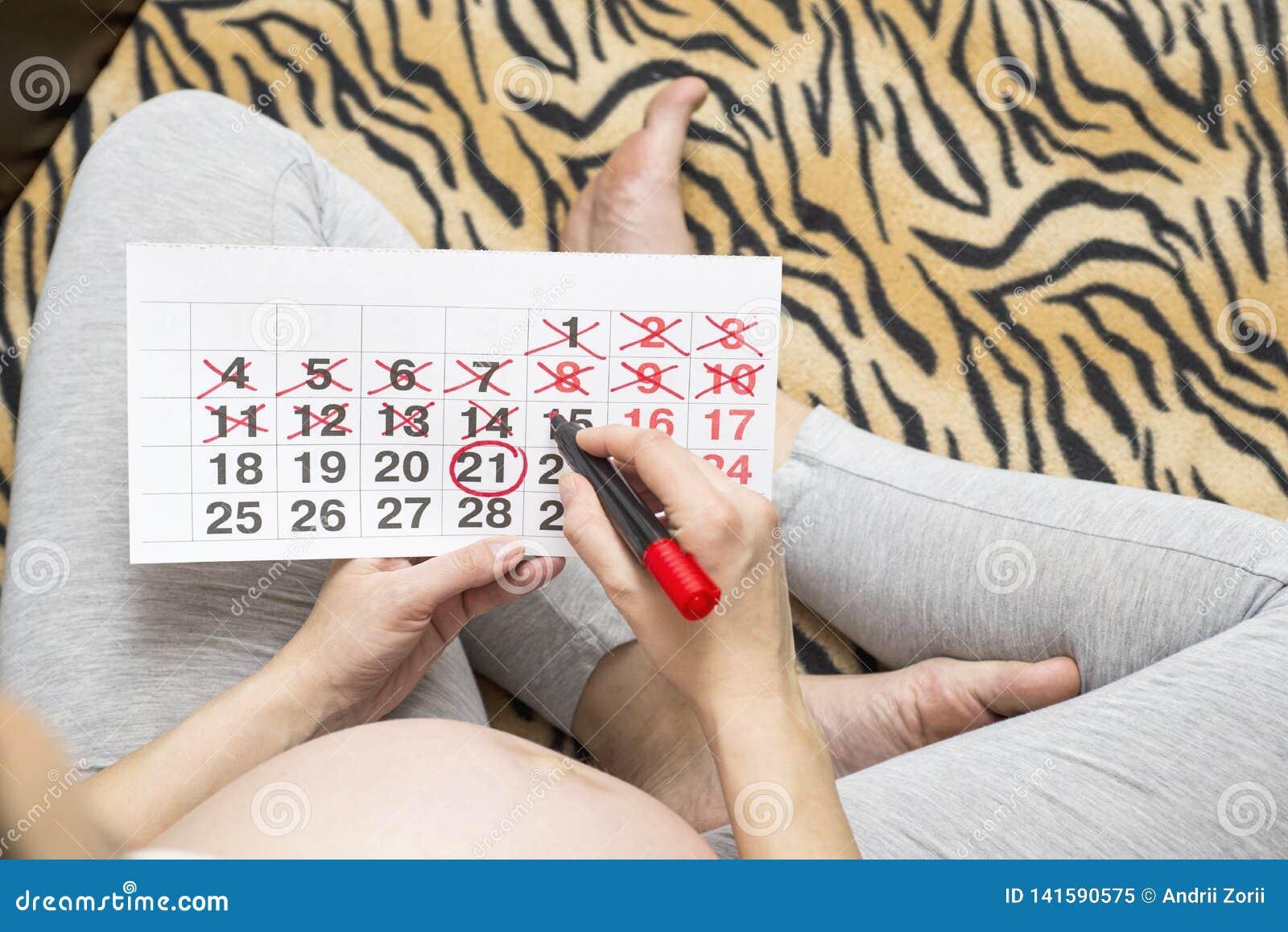 Mulher gravida nova com a pena e o calendário de ponta sentida vermelha Mulher gravida nova que conta dias com o calendário ao na
