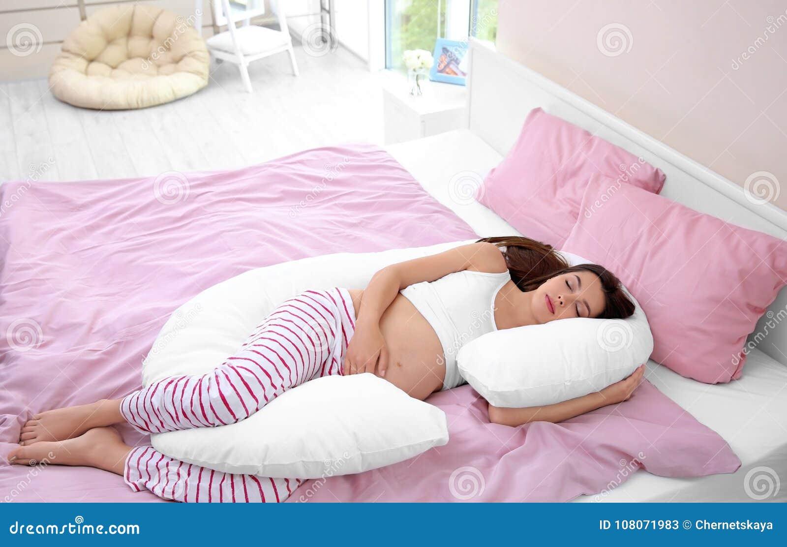 Mulher gravida nova que dorme no descanso de maternidade